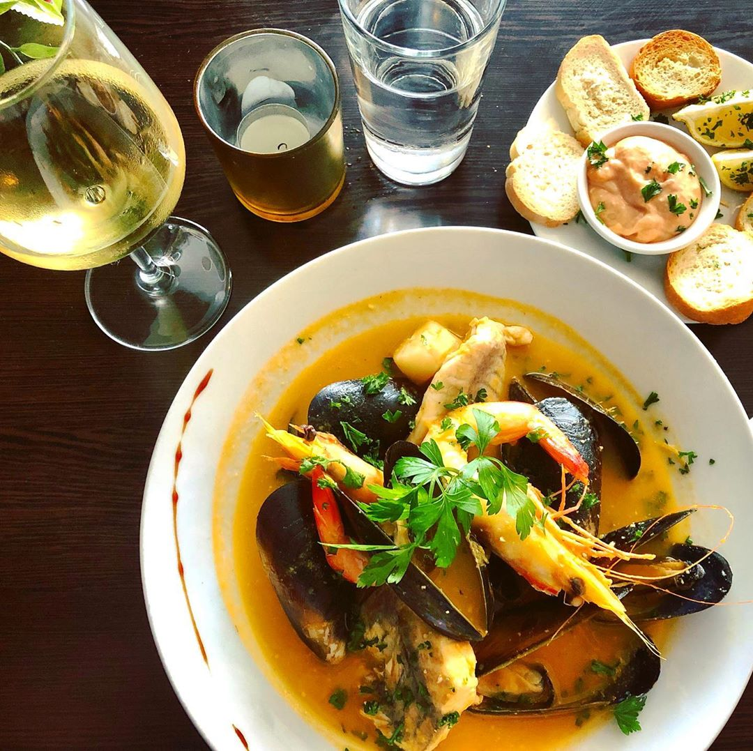 A bowl of bouillabaisse, a plate of baguette and dip and a glass of wine on a table at The French Bistrot