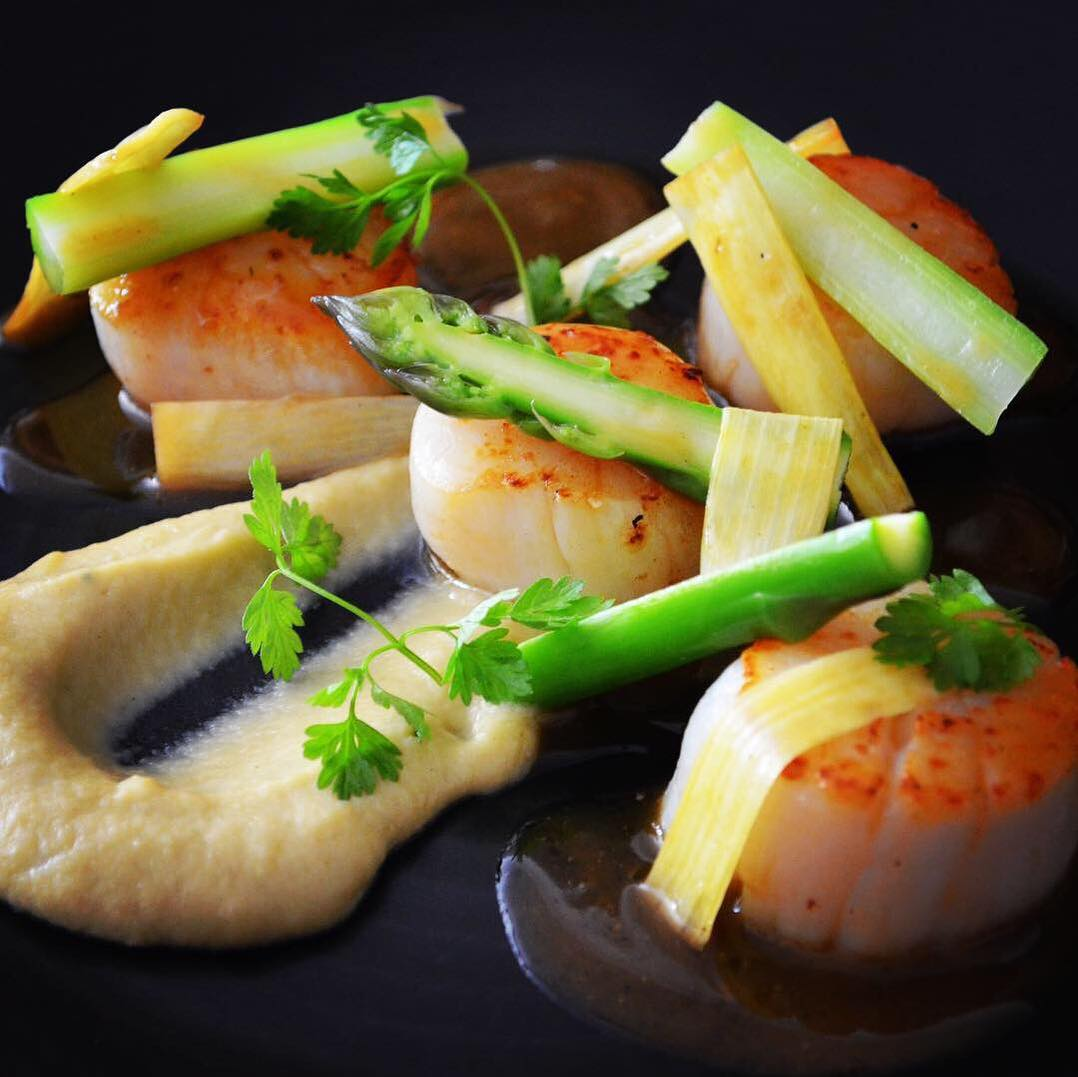 Seared scallops with asparagus and burnt tosazu butter on a black plate at Cocotte Dining French Restaurant
