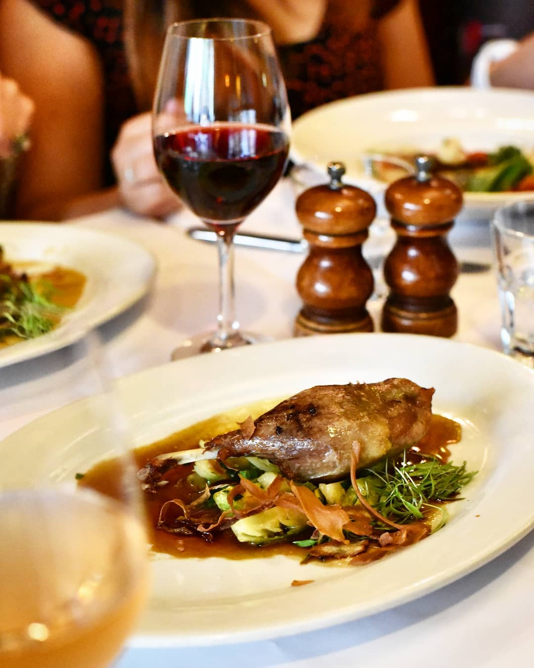 Confit duck leg on a bed of vegetables with jus on a table with wine at Bistrot D'Orsay French restaurant