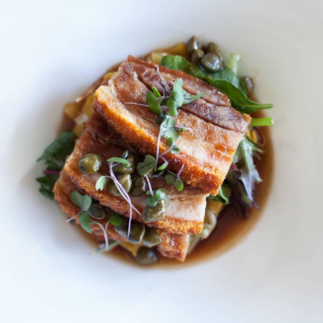 Three slices of crispy pork belly on a bed of mixed leaves and herbs on a white plate, surrounded by jus