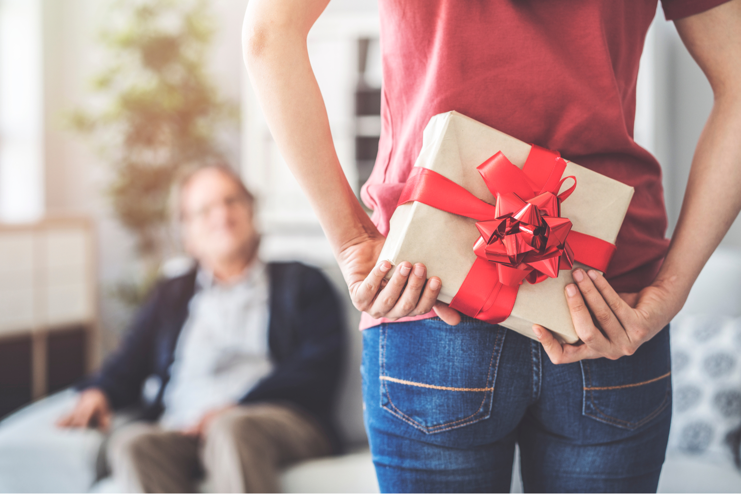 Young woman standing in front of her dad, holding a Father's Day gift behind her back