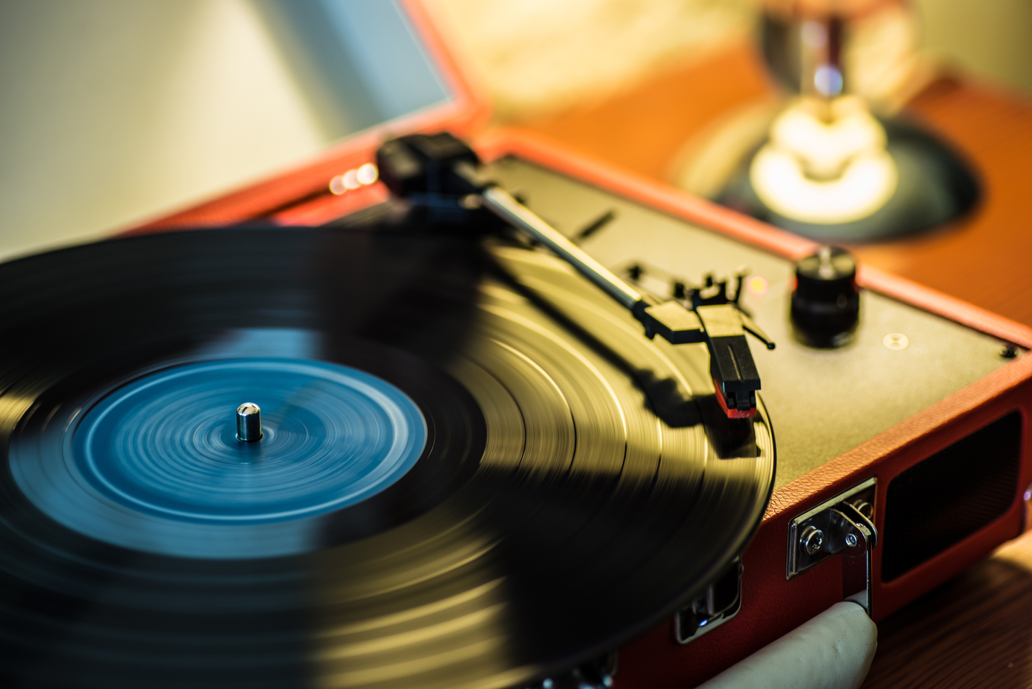 A vinyl record spinning on a suitcase record player