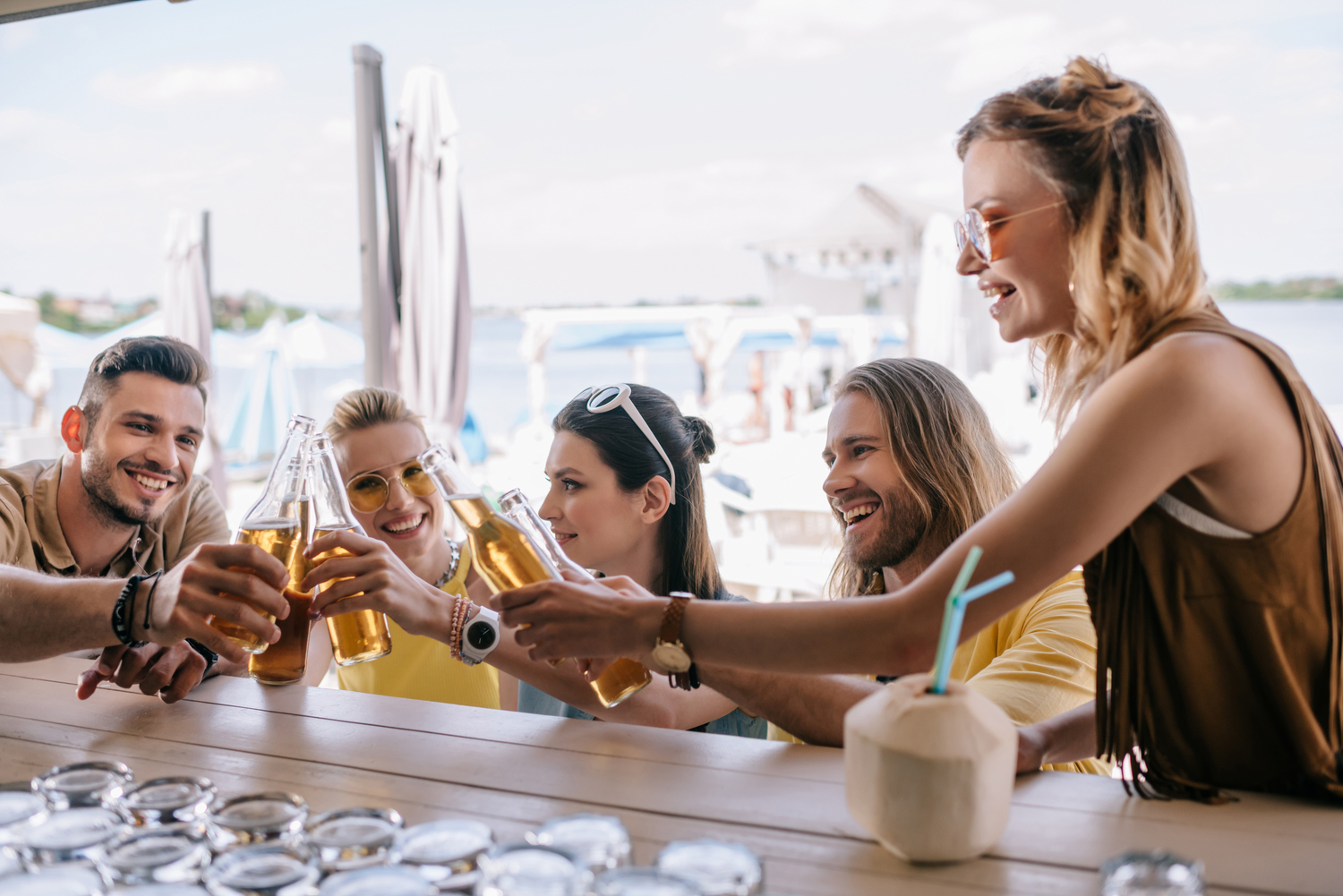 Five young friends clinking beer bottles at a beachside bar in Bali