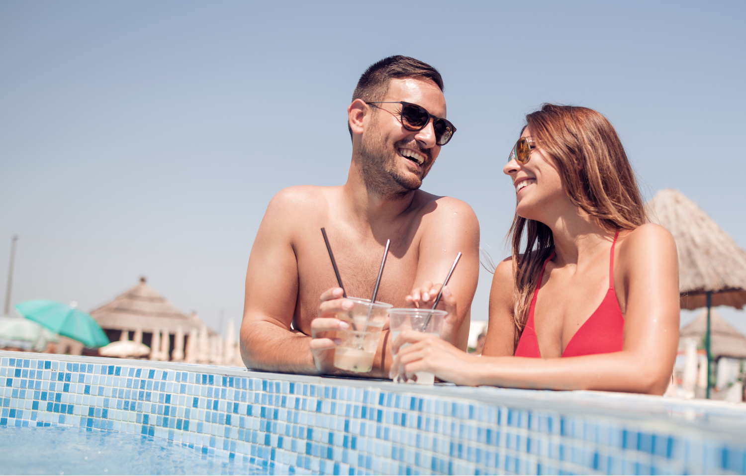 Young couple smiling at each other while drinking iced tea by the pool at an adults-only Bali resort
