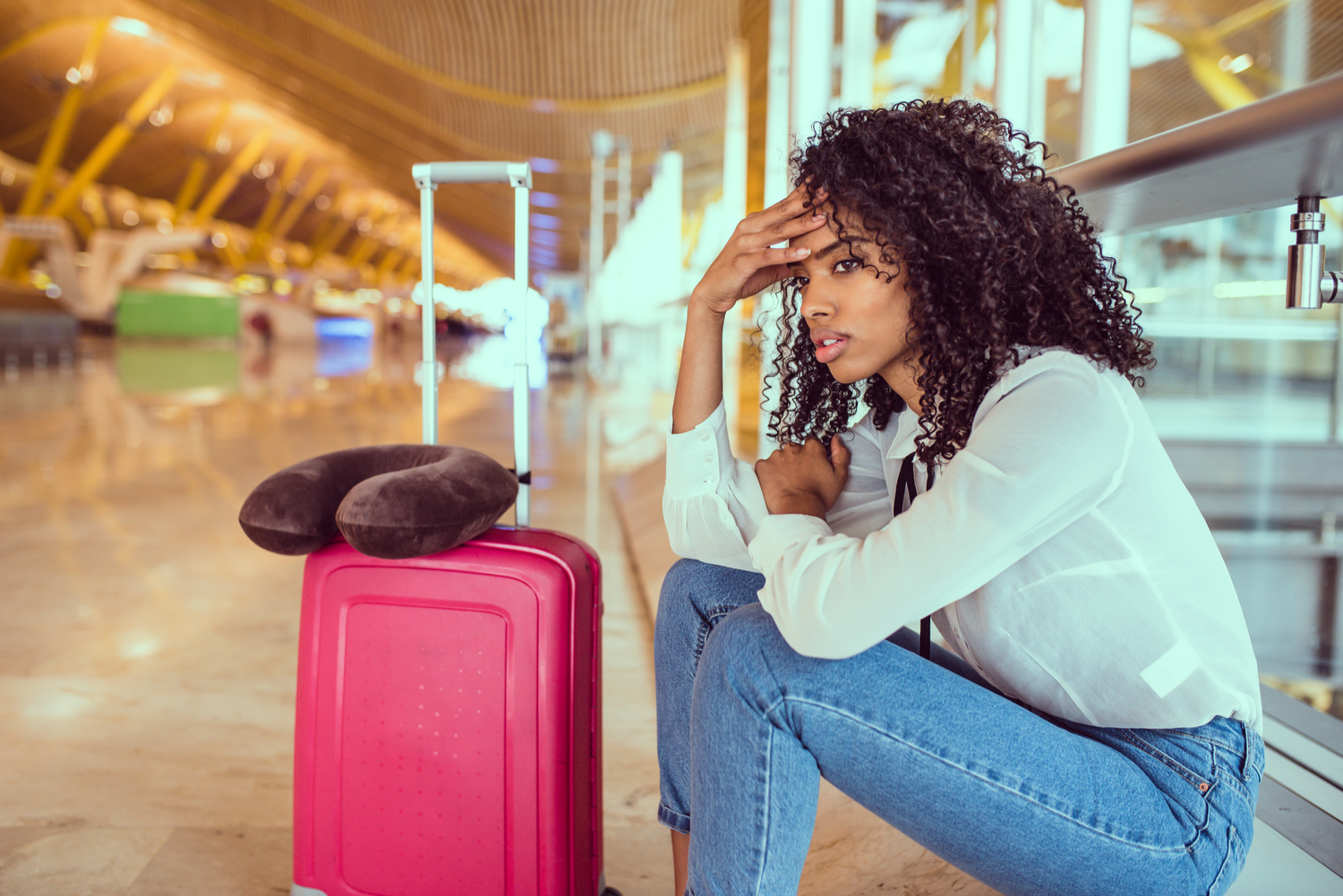 Young brunette woman sitting on the floor at an airport next to her suitcase looking stressed and unhappy