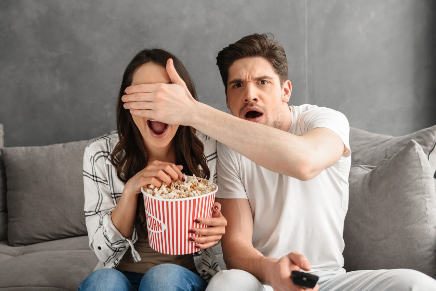 A young couple are sitting on a grey sofa watching a horror movie. The woman is eating popcorn and the man is covering her eyes