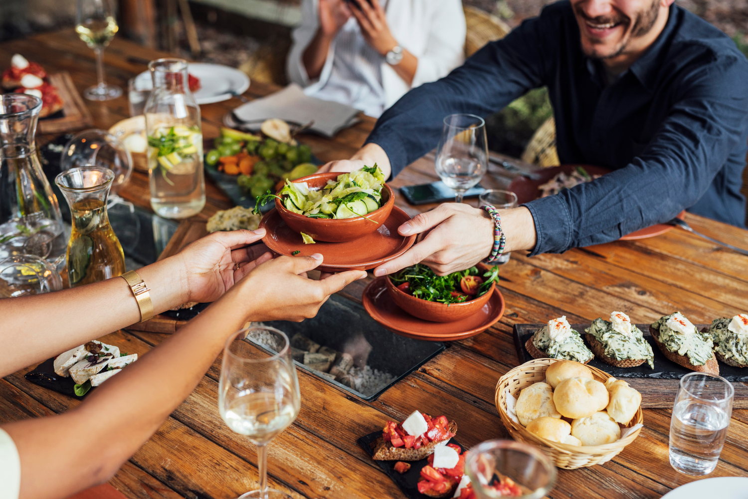 young man passing a bowl of green vegetables to a young woman over a table full of food at a vegetarian restaurant