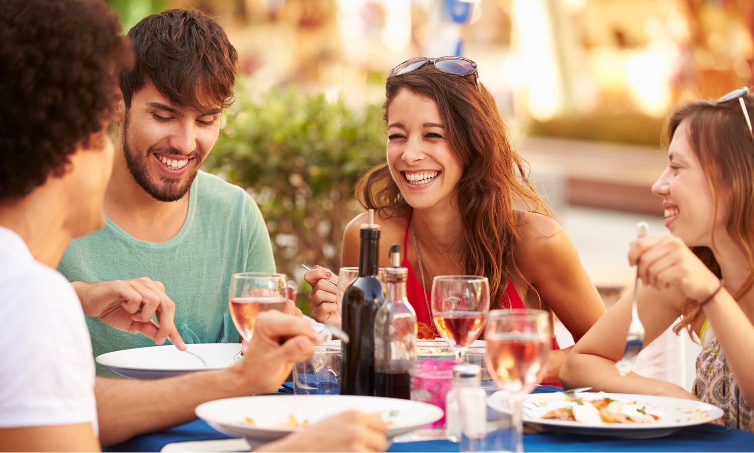 Group of four young friends laughing over lunch and glasses of rose wine