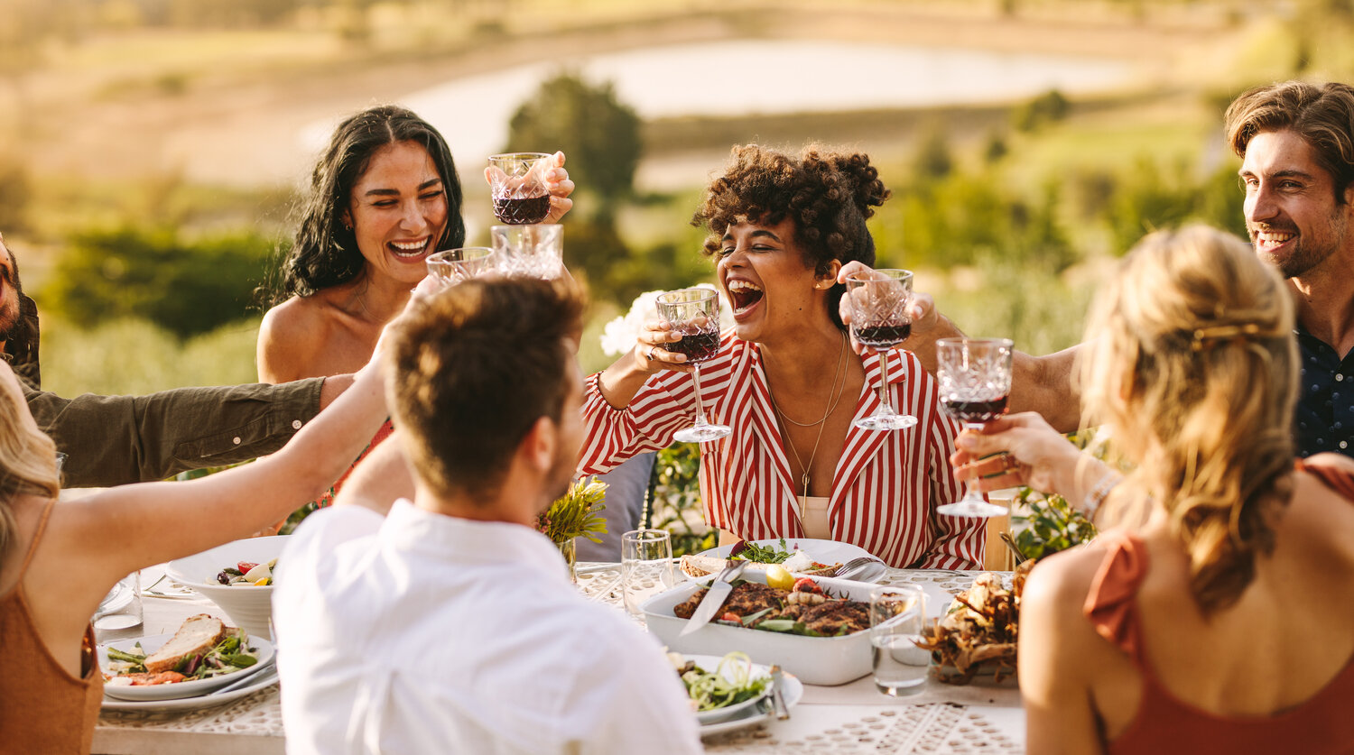 A group of young friends laughing as they toast with red wine over a table full of food