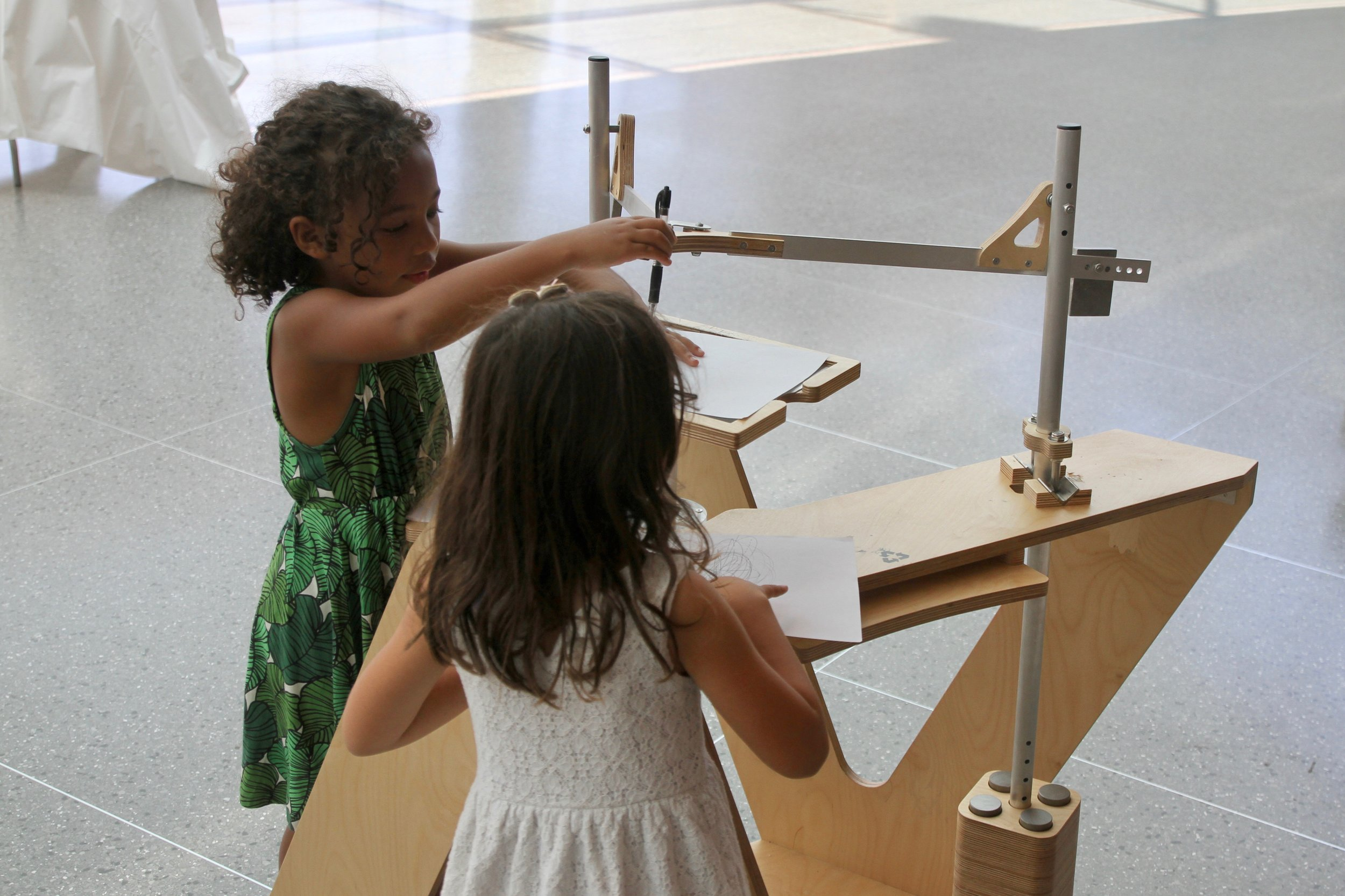 Children experiencing the harmonograph during its time in the foyer of the Brooklyn Museum.