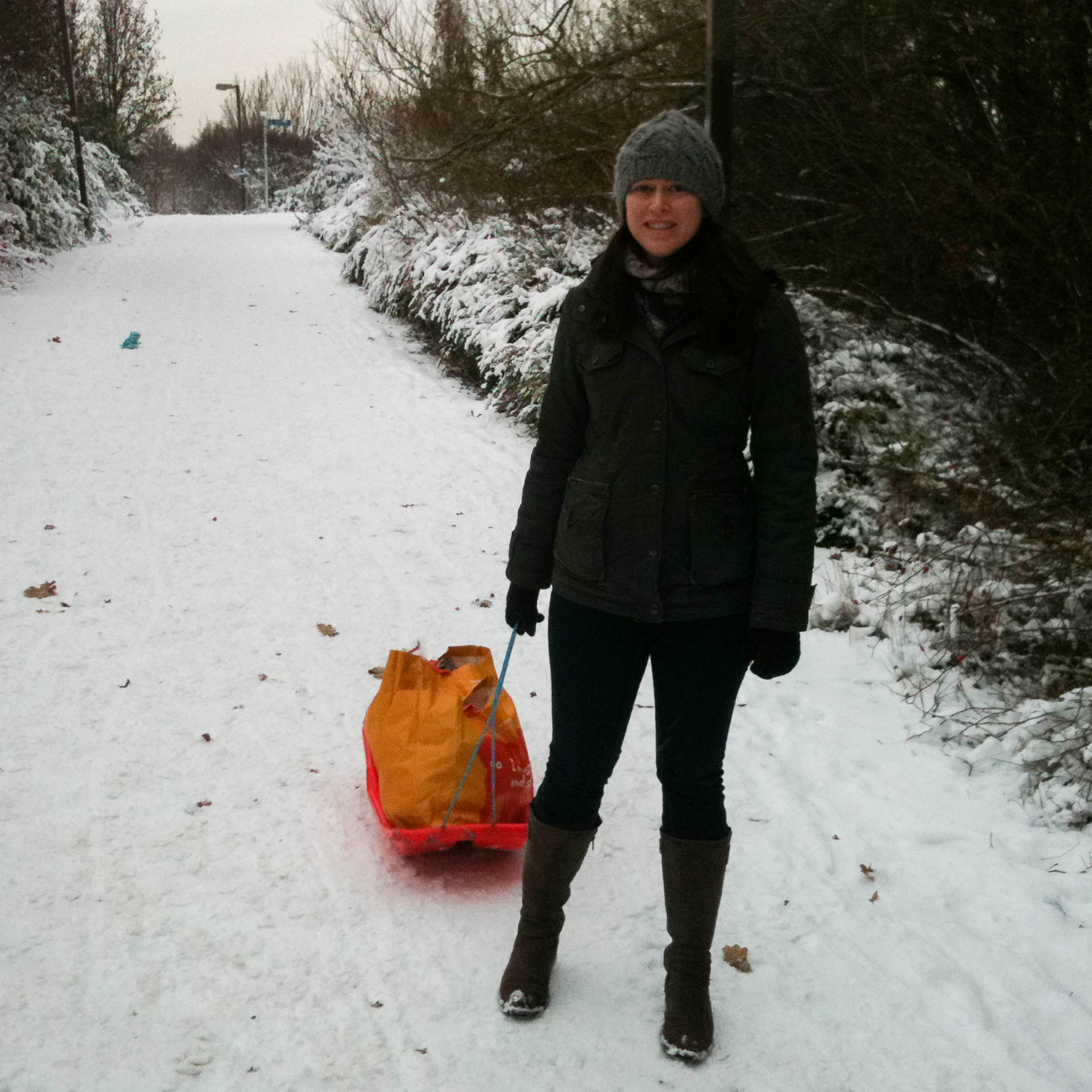 Woman pulling a sled that is carrying a bag of groceries down a snowy slope