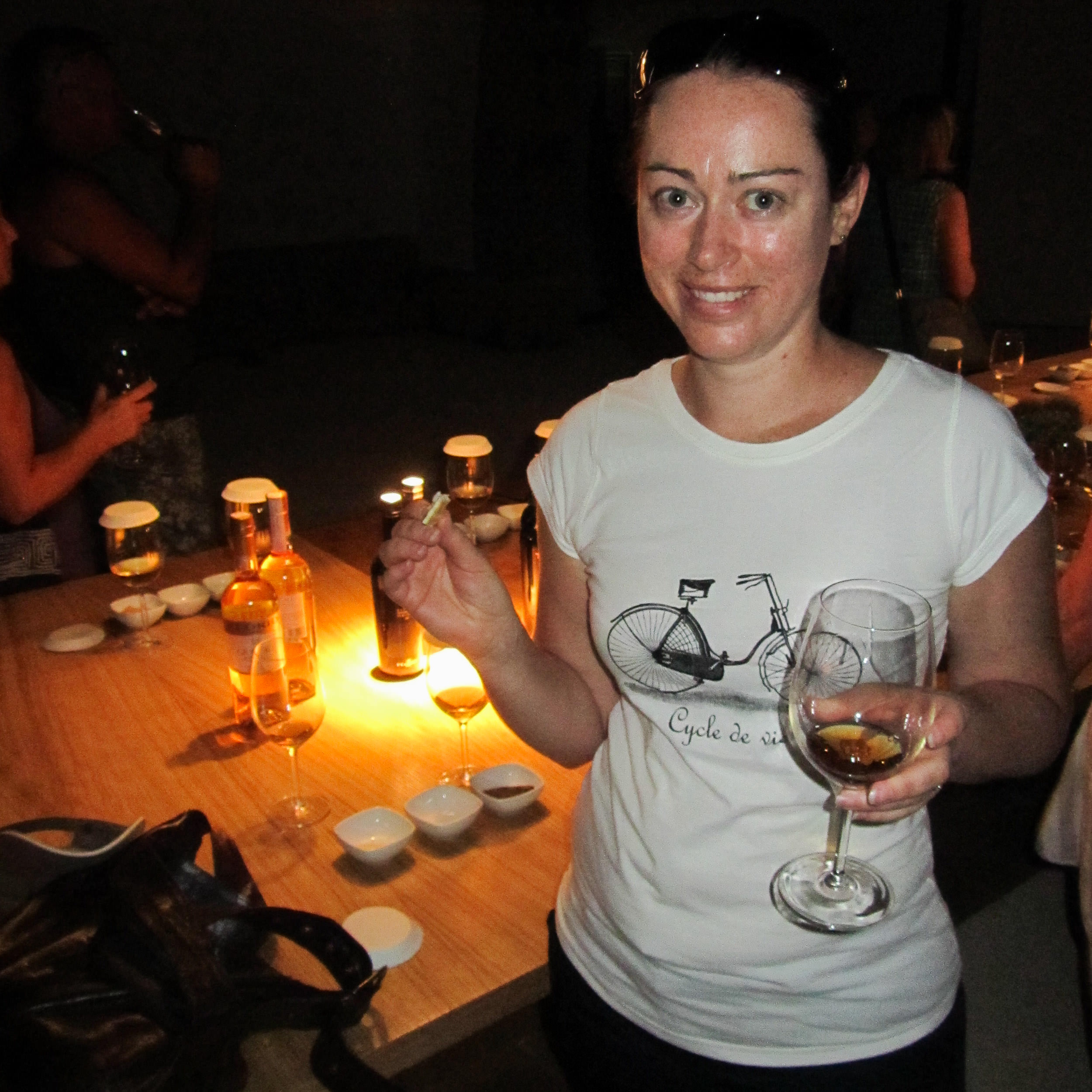 woman looking at camera while holding a glass of wine and cheese