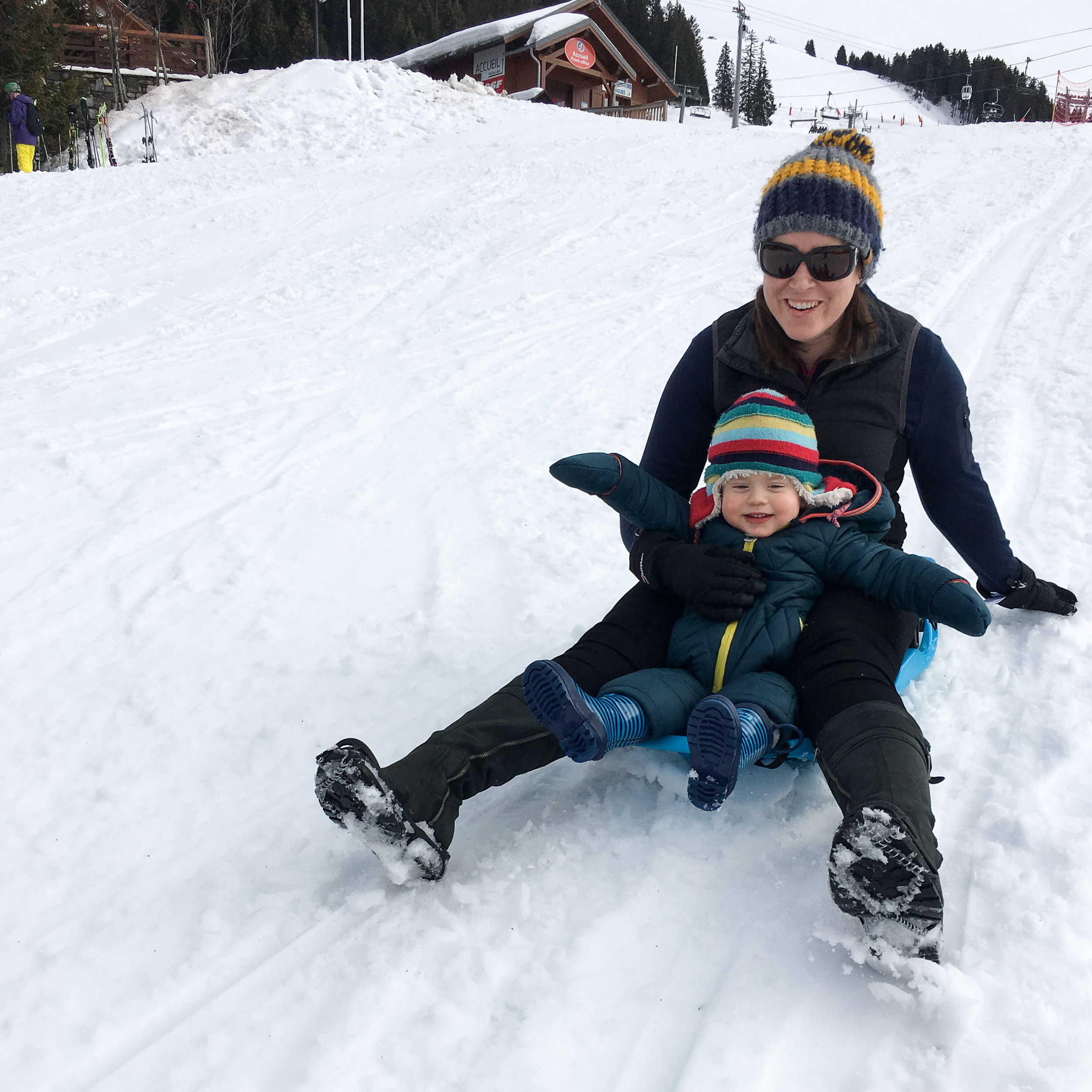 Woman and little boy sledding down a snowy slope