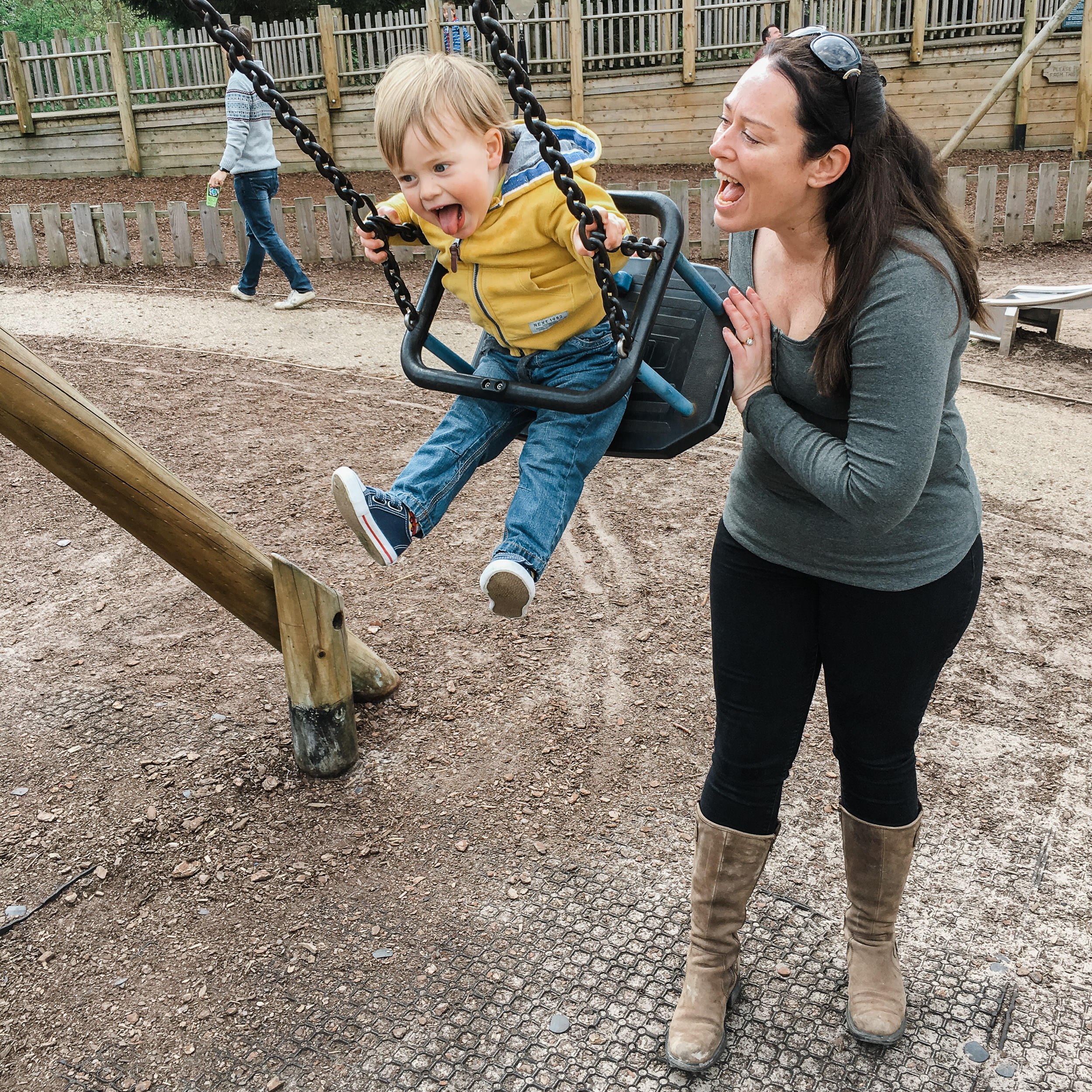 Woman pushing little boy on swing and laughing