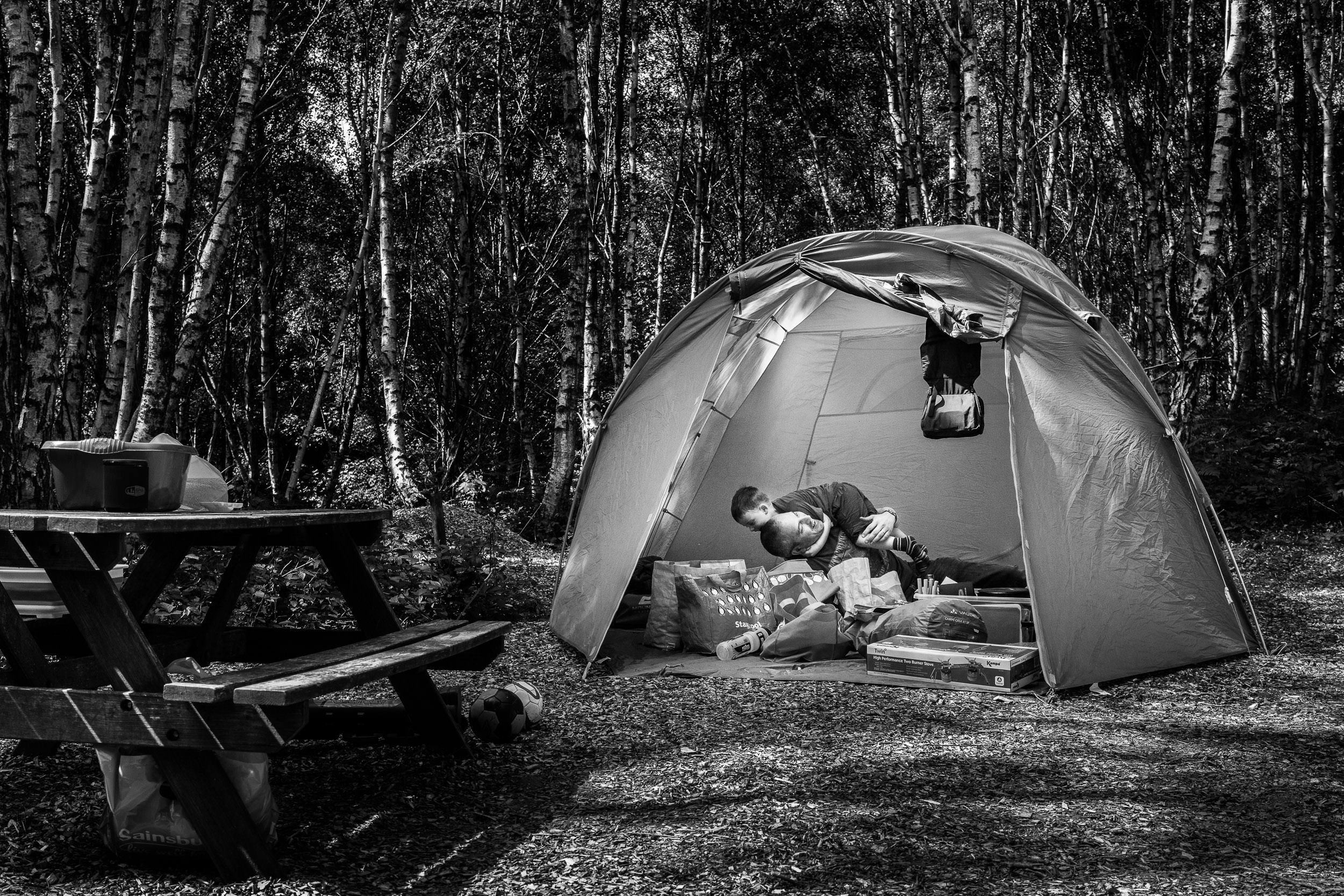 Father and son play around inside a tent while camping