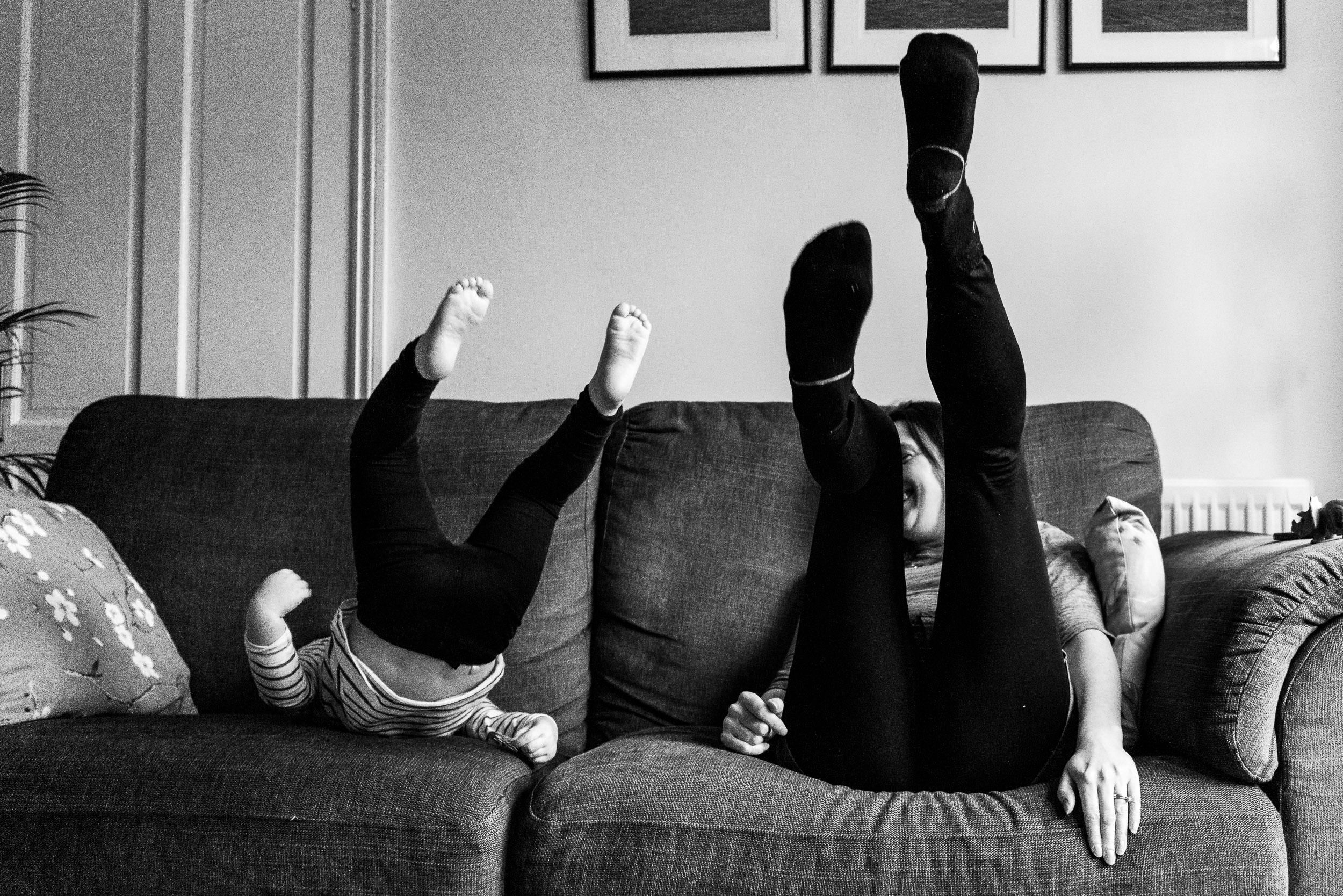 Mother and daughter on sofa with their legs in the air