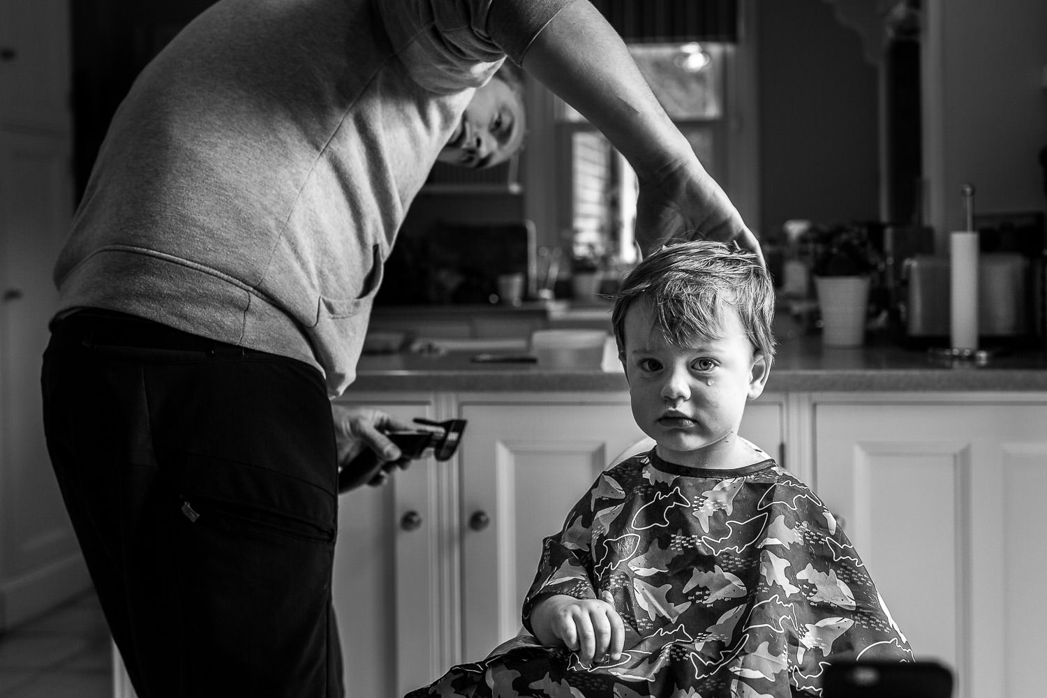 Little boy sheds a tear as father cuts his hair