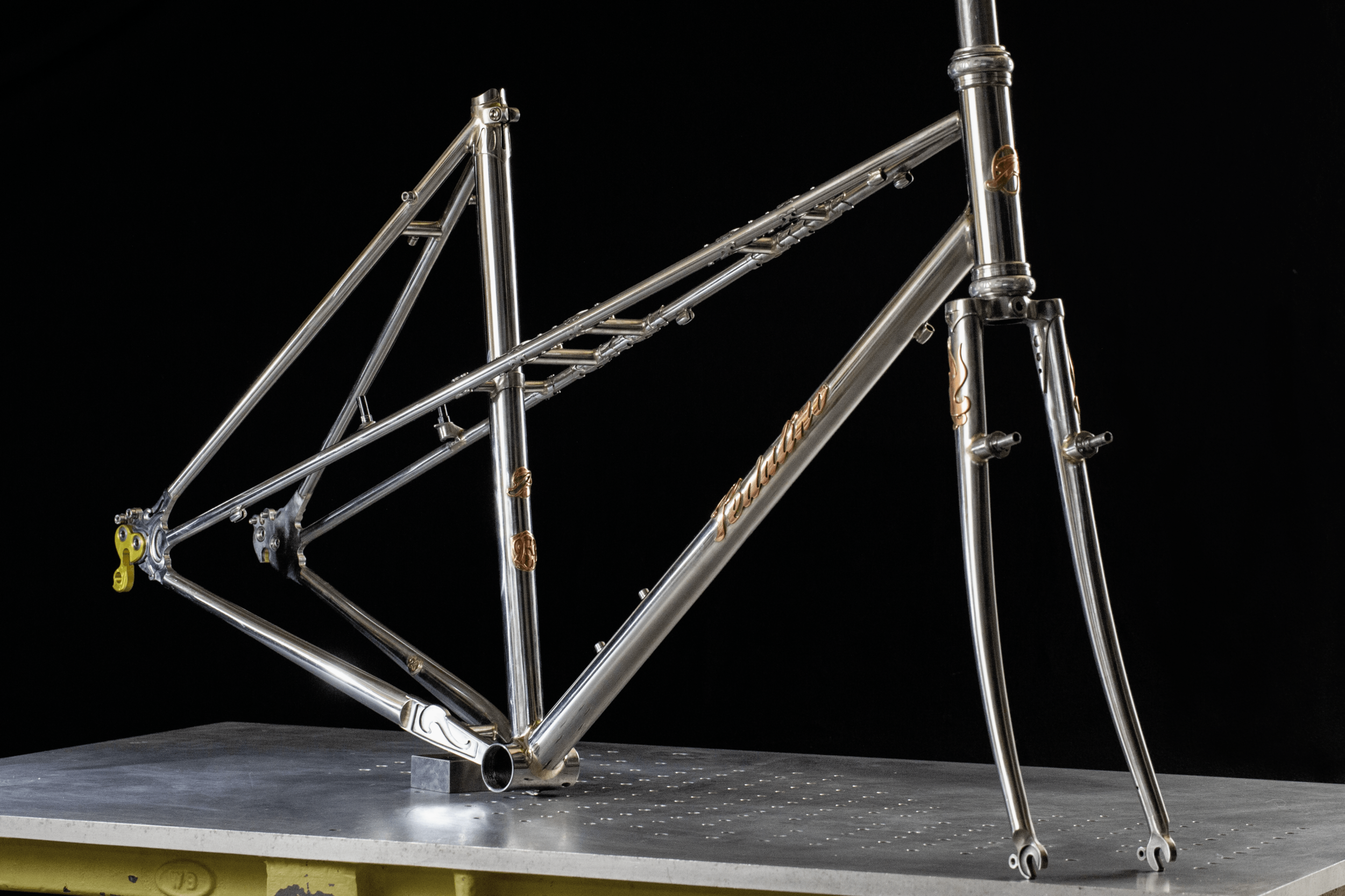 Stephen's 953 Mixte Frameset - Reynolds 953 stainless steel frame and fork with in-house CNC machined dropouts, chain stay plate, and bridge reinforcement sleeves. Raw polished finish with copper badges.