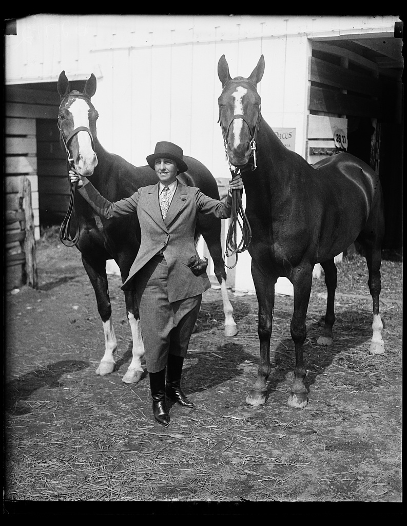 """Wife of New York department store magnate captures first and second prizes at Washington Horse Show. Mrs. Bernard Gimbel, wife of the New York department store magnate, and her horses Capt. Doane (left) and welcome with whom she captured first and second prizes in the Ladies Hunters class at the National Capital Horse Show today. Capt. Doane is the $12,000 dollar horse who has been capturing many blue ribbons in eastern horse shows recently,"" Harris & Ewing, photographer, 18 May 1928. Library of Congress LC-H2- B-2712"