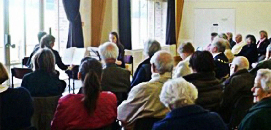 """Wednesday, 20 March 2019: Duo Antipodes Teatime Concert at St Christopher's Church - Manus Noble, playing Guitar, and Jehanne Bastoni, on Cello, gave a concert in the afternoon to about 50 elderly people from residential homes around Haslemere, and others brought from their homes by friends. The programme was very similar to the musical journey the Duo took Grayswood Primary School children on at a workshop in the morning, with music from Italy by Luigi Boccherini, Andaluza by Enrique Granados from Spain, a fairy tale tune from Japan, a beautiful Irish piece called Starry Night and an African piece called Benga Beat by Gary Ryan. In addition they played Nana by Manuel de Falla and the peaceful Spiegel im Spiegel by Arvo Part. This concert was very much enjoyed by all our guests, many of whom cannot go out in the evenings, and they are all looking forward to our Outreach Day next year. These concerts were in part made possible by Haslemere Town Council through the """"Penny Ha'Penny Trust"""" and funded in part by HHH Concerts as part of their outreach programme."""