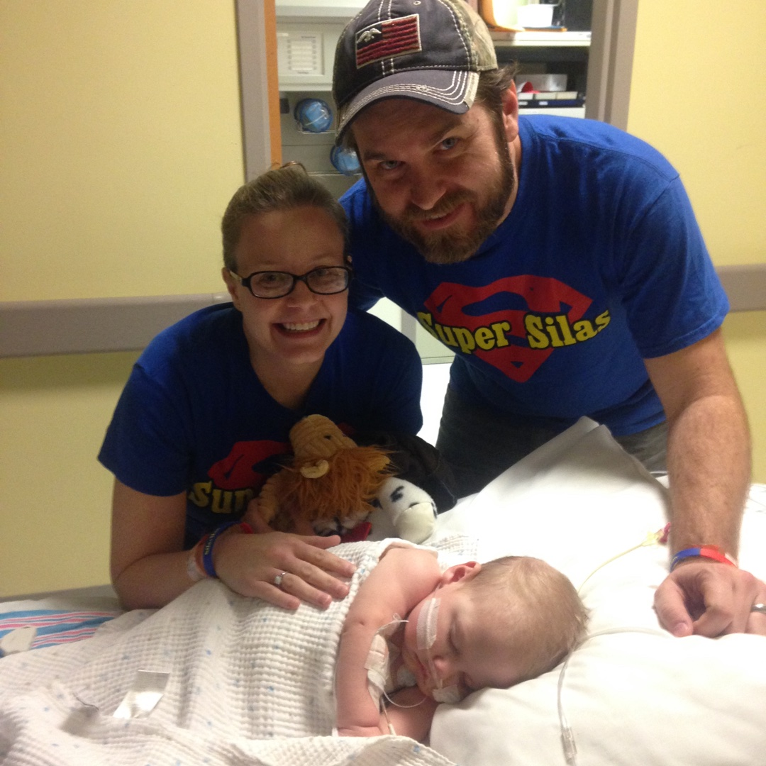 Silas in bed with Amanda and Chris smiling and wearing Super Silas shirts | Heart Transplant Story