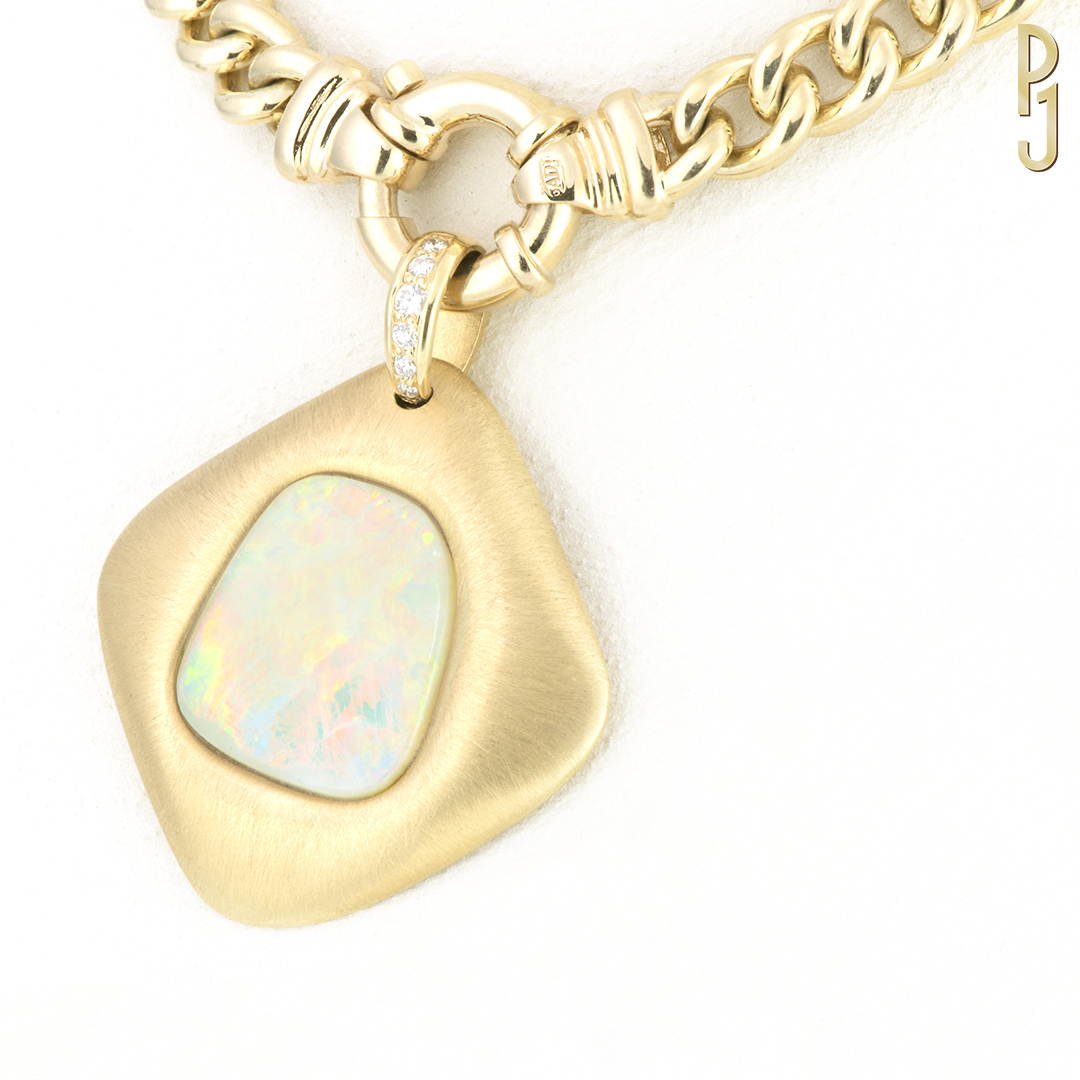 WHITE OPAL - Pendant: White opal set in 18ct. yellow gold with a brushed finish plus 6 diamonds = 16pts.Origin: Coober Pedy, South AustraliaDesigned & handmade by Philip.