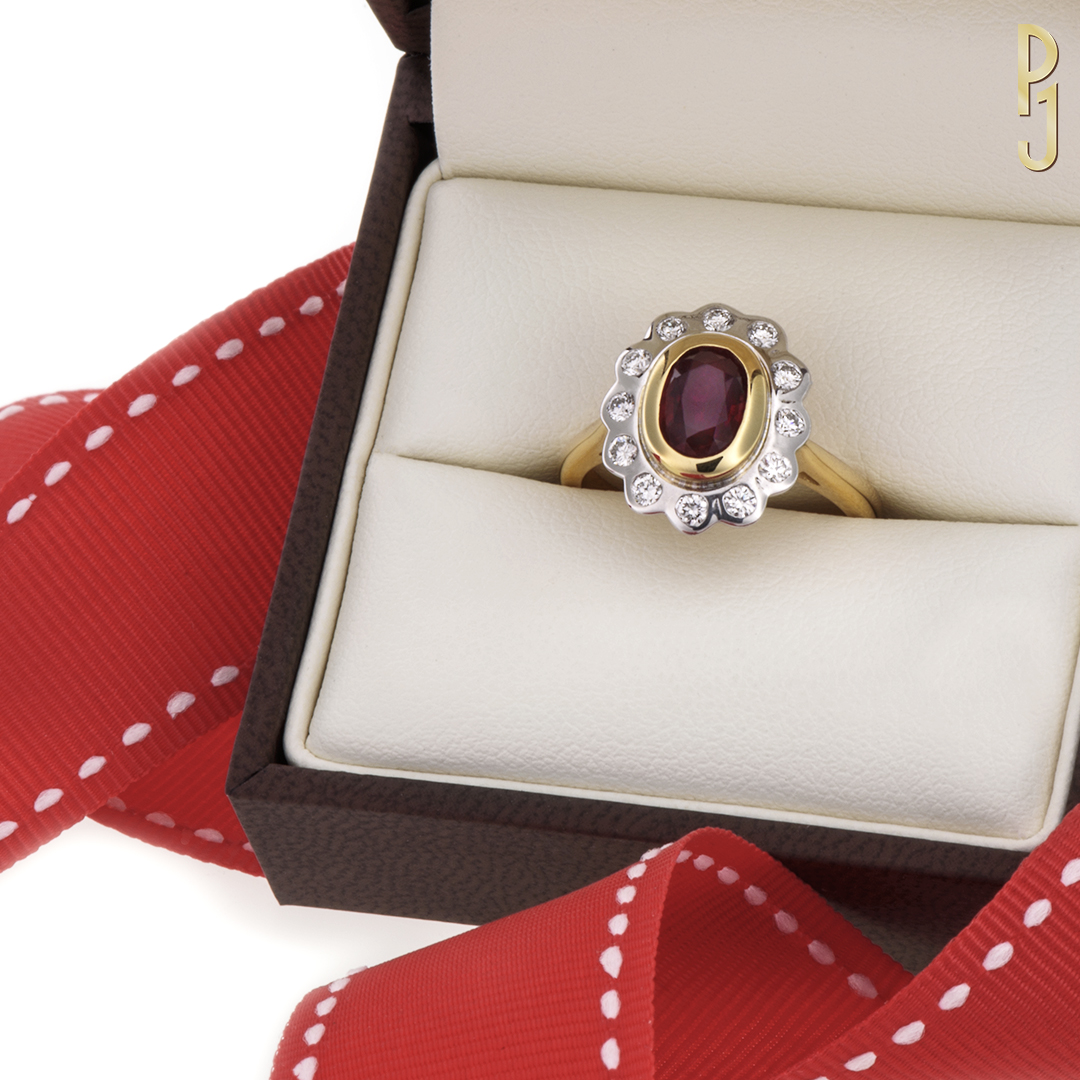 AFRICAN RUBY - Ring: African ruby, oval shape, 1.36ct. surrounded by 12 x 3pt. diamonds set in 18ct. yellow and white gold