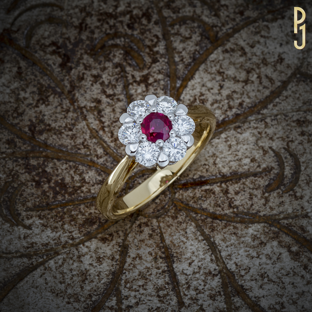 BURMESE RUBY - Ring: Burmese ruby, round, 33pts plus 6 diamonds = 76pts. set in 18ct. yellow and white gold.