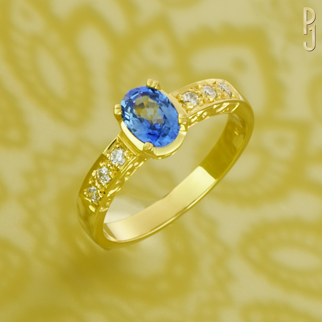 CEYLON BLUE - Ring: Ceylon sapphire, oval shape, 1.1ct. plus diamonds 6 = 18pts. set in 18ct. yellow gold. The sides of the ring are engraved.