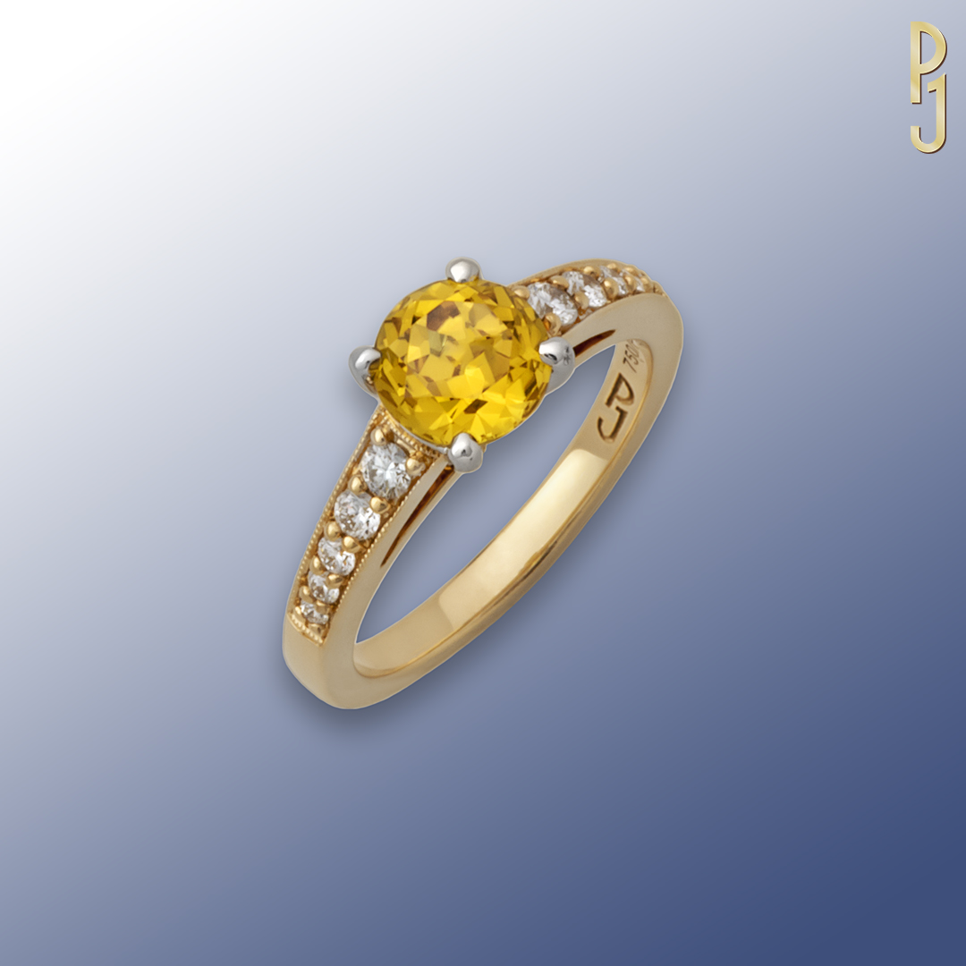 AUSTRALIAN YELLOW - Ring: Australian yellow sapphire, round, 1.76ct. in a platinum setting plus 10 tapering diamonds = 23pts. set in 18ct. yellow gold. The band is finished with a fine milgrain edge.