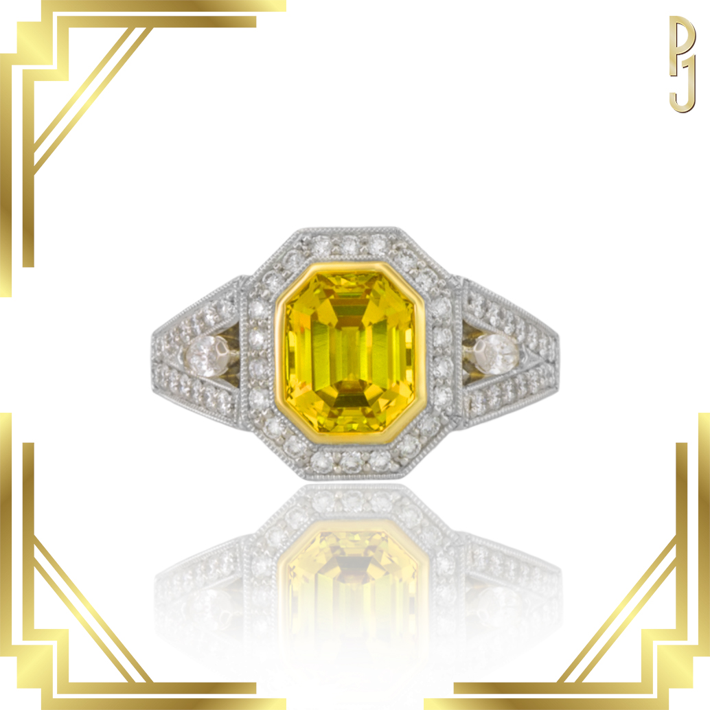AUSTRALIAN YELLOW - Ring: Australian yellow sapphire, emerald cut, 2.62ct. plus diamonds = 43pts. set in 18ct. yellow gold and platinum. The setting is finished with a fine milgrain edge.An Art Deco inspired piece designed by Philip.