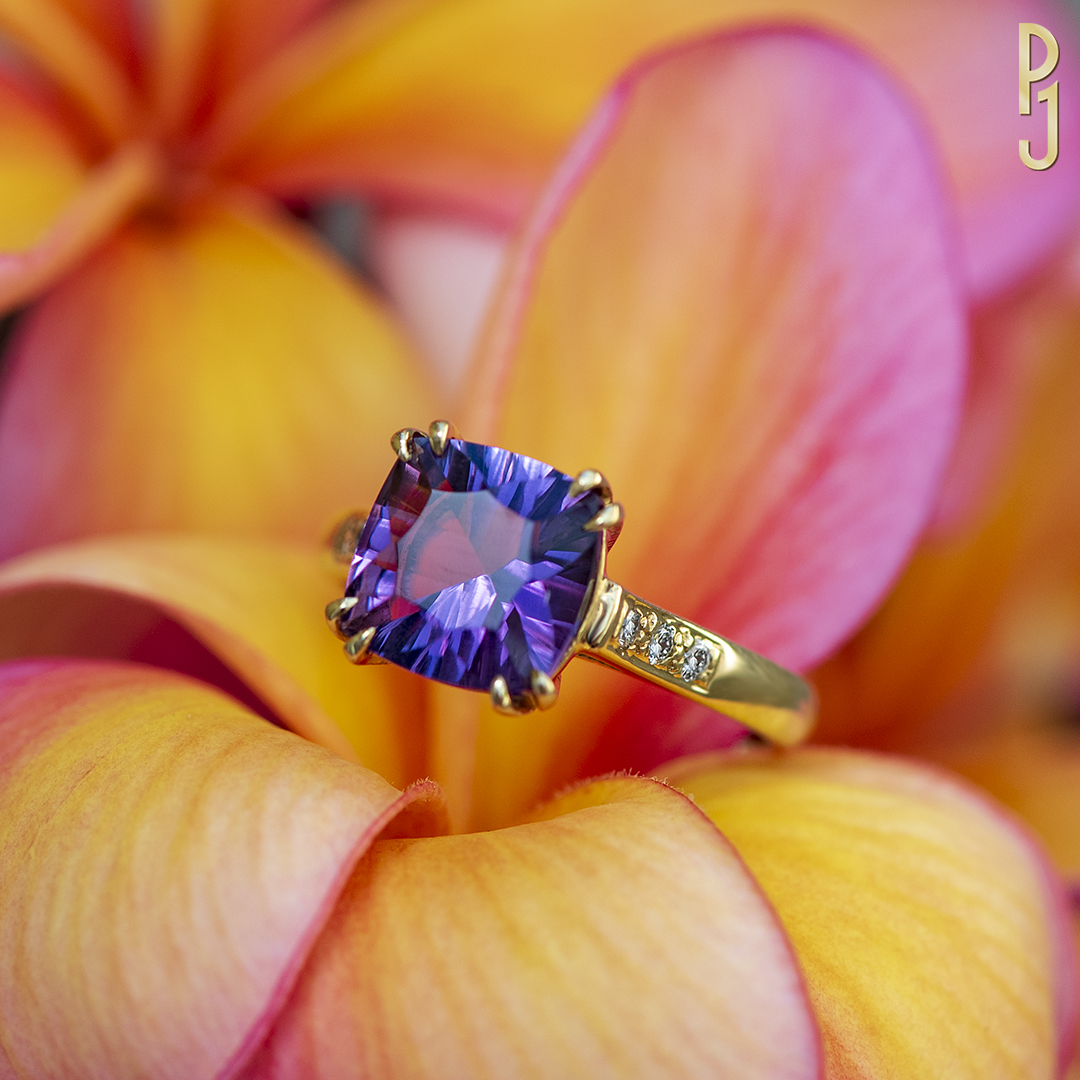 AMETHYST - Amethyst is the birthstone of those born in February.Ring: Amethyst, laser cushion cut, 2.57ct. plus 6 pavé set diamonds = 12pts. set in 9ct. yellow gold.Designed and handcrafted by Philip.