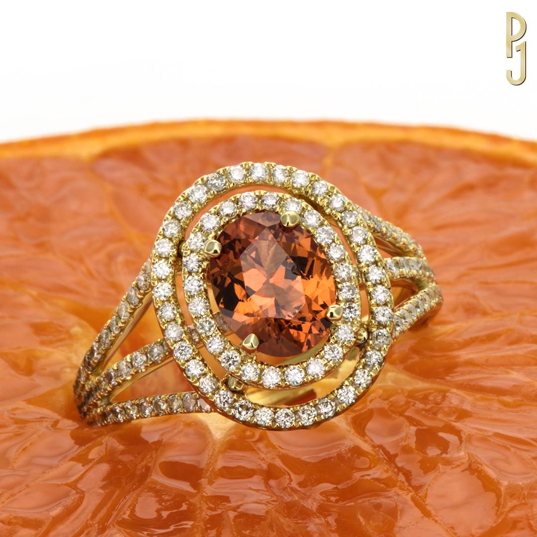 MANDARINE GARNET - Garnet is the birthstone of those born in January.Ring: Deep orange mandarin garnet, oval cut, 1.42ct. plus 145 diamonds = 65pts. set in 18ct. yellow gold.