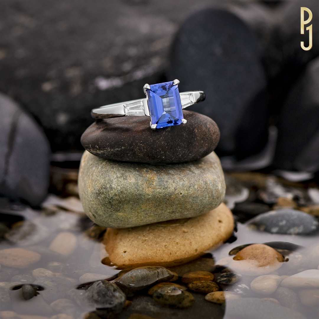 TANZANITE - Tanzanite is the birthstone of those born in December.Ring: Tanzanite, emerald cut, 2.1ct. plus two tapered baguette diamonds = 36pts. set in 18ct. white gold.
