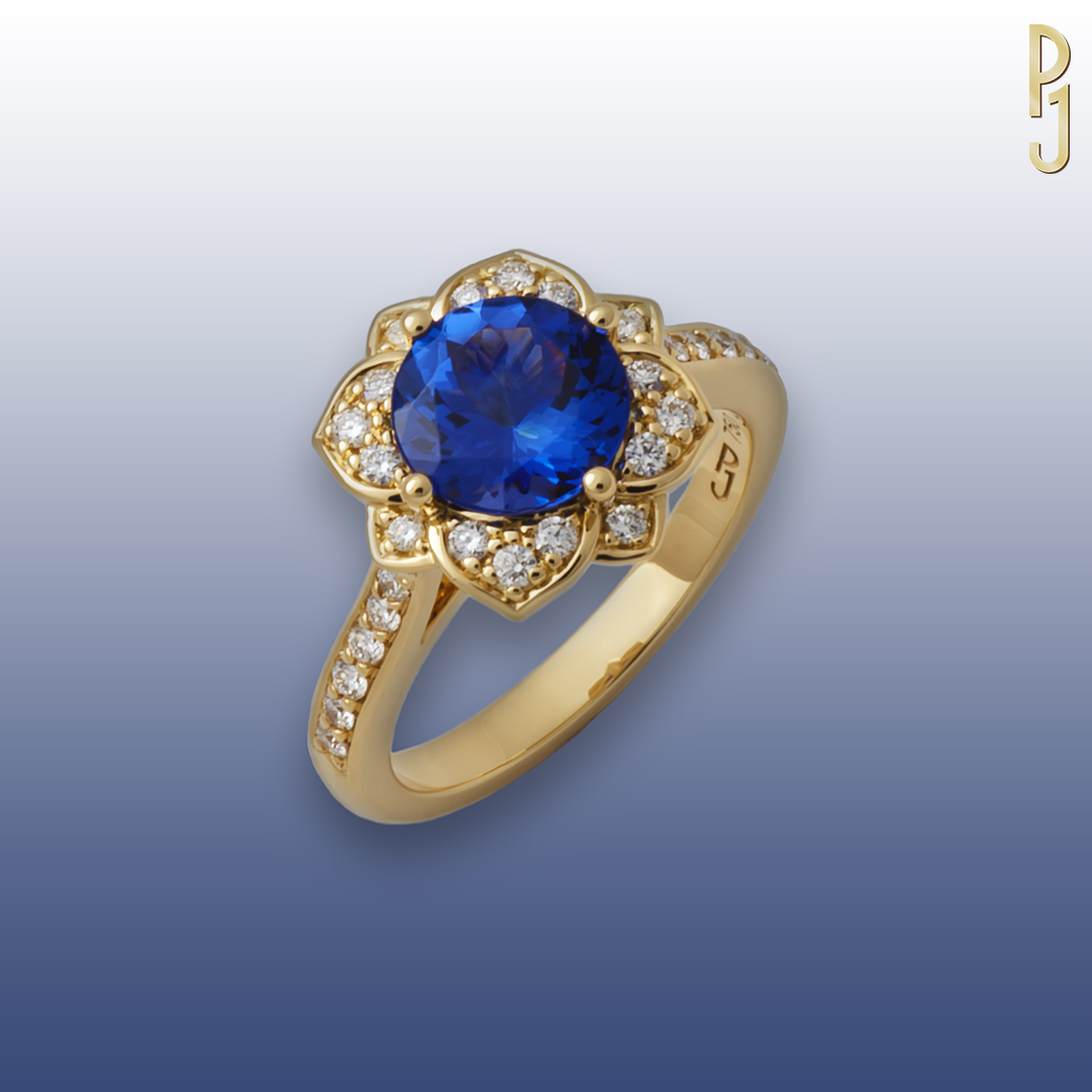TANZANITE - Ring: Tanzanite, round, 1.68ct. plus 28 diamonds = 34pts. set in crafted 18ct. yellow gold.Designed and handcrafted by Philip.