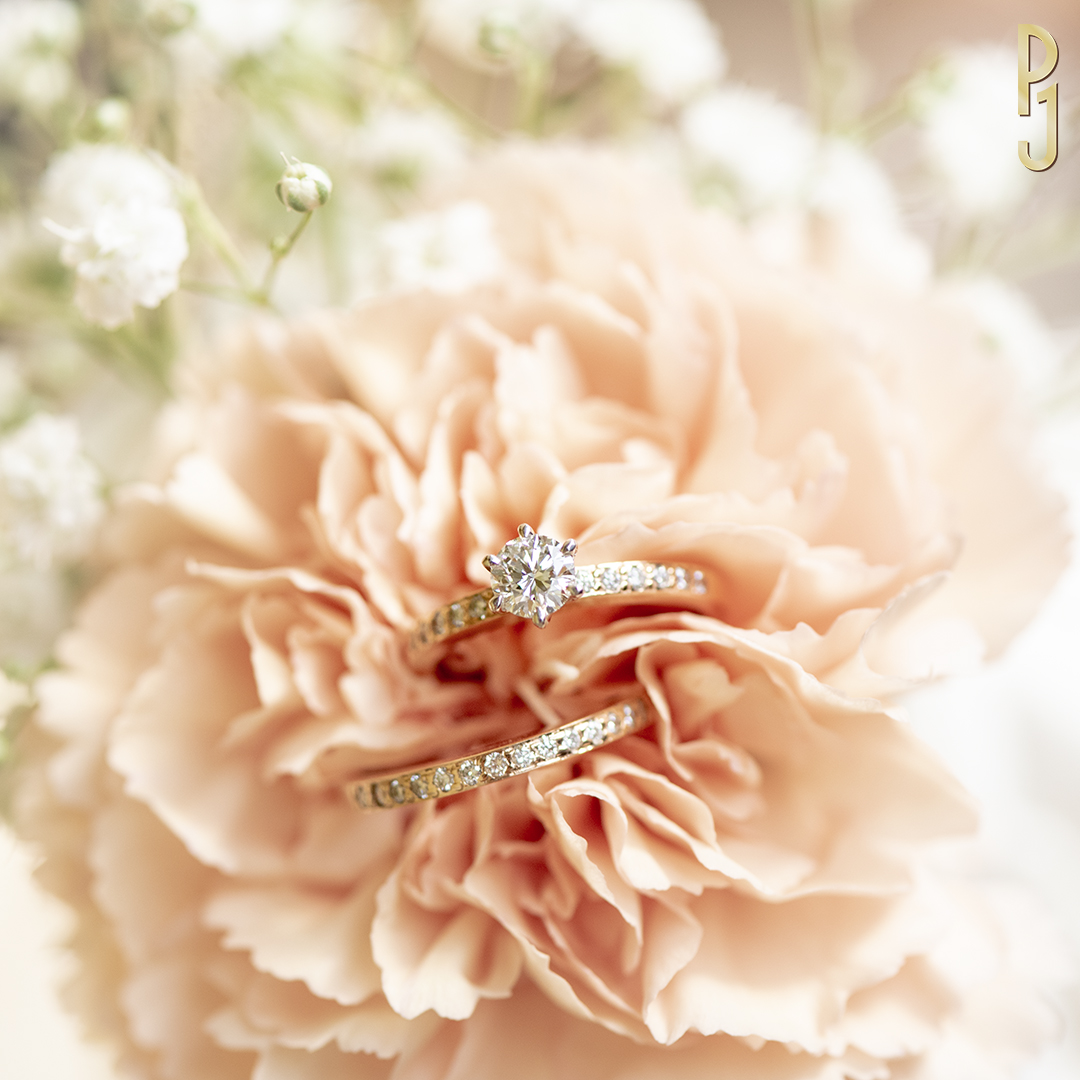 DIAMOND PAVÉ BRIDAL SET - A six-claw platinum setting allows the centre 50pt. G/SI1 diamond to float above a narrow 18ct. rose gold diamond pavé band. A matching wedding band and eternity band is also available. Designed and handcrafted by Philip.