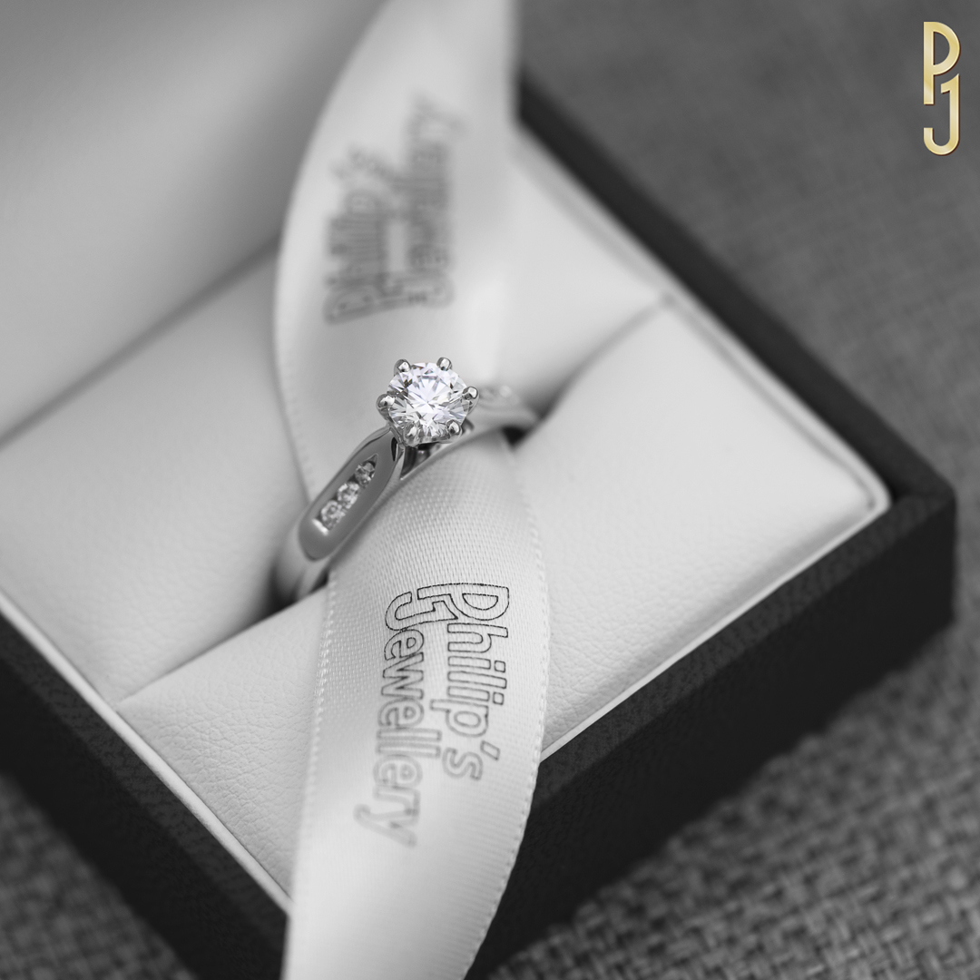 IDEAL SOLITAIRE - This ring is made of 18ct. white gold showcasing a 50pt. G/SI1 diamond with three channel set diamonds on each side.