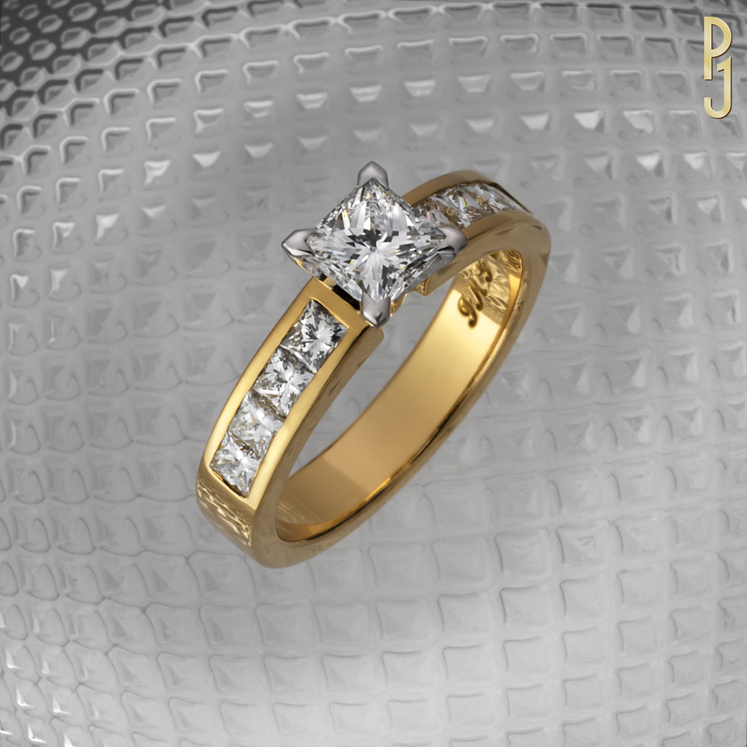 PRINCESS - This 78pt F/SI1 diamond centre stone is accompanied by another 8 princess cut diamonds = 75pts on the shoulders of this 18ct yellow gold ring.Designed and handcrafted by Philip.