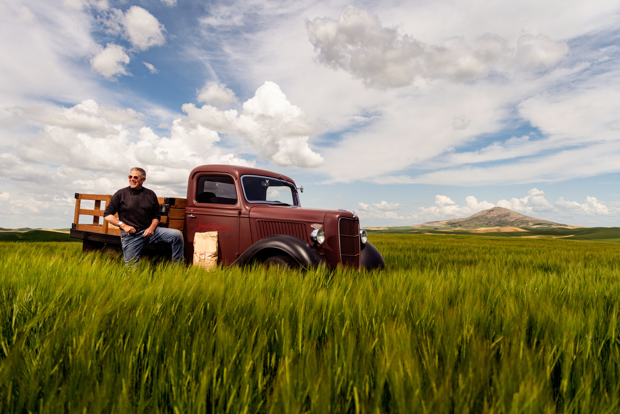 Bill with red vintage Ford truck with Steptoe Butte in distance