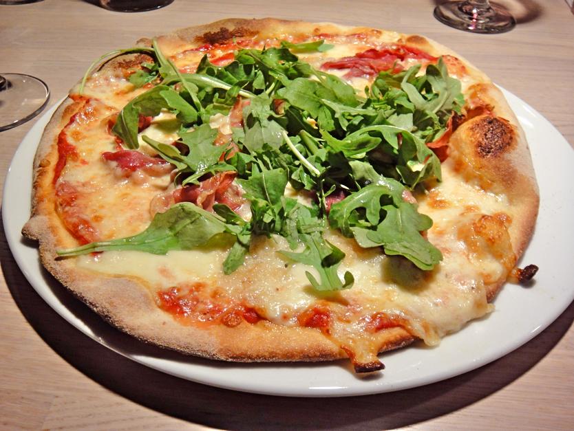Michelangelo-pizza: rucolaa, ilmakuivattua kinkkua ja mozzarellaa