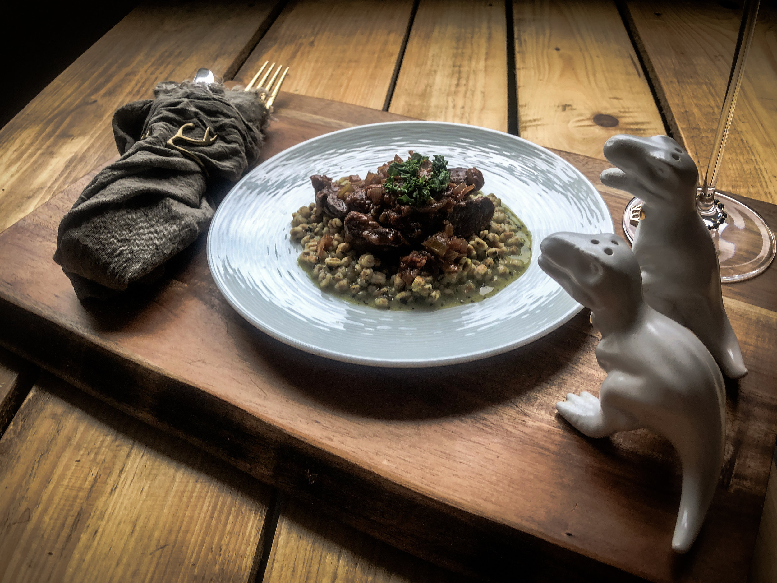 Wine braised venison heart served over pesto spelt, garnished with kale and paired with a Malbec. Salt and pepper to taste (via dinosaur shakers).