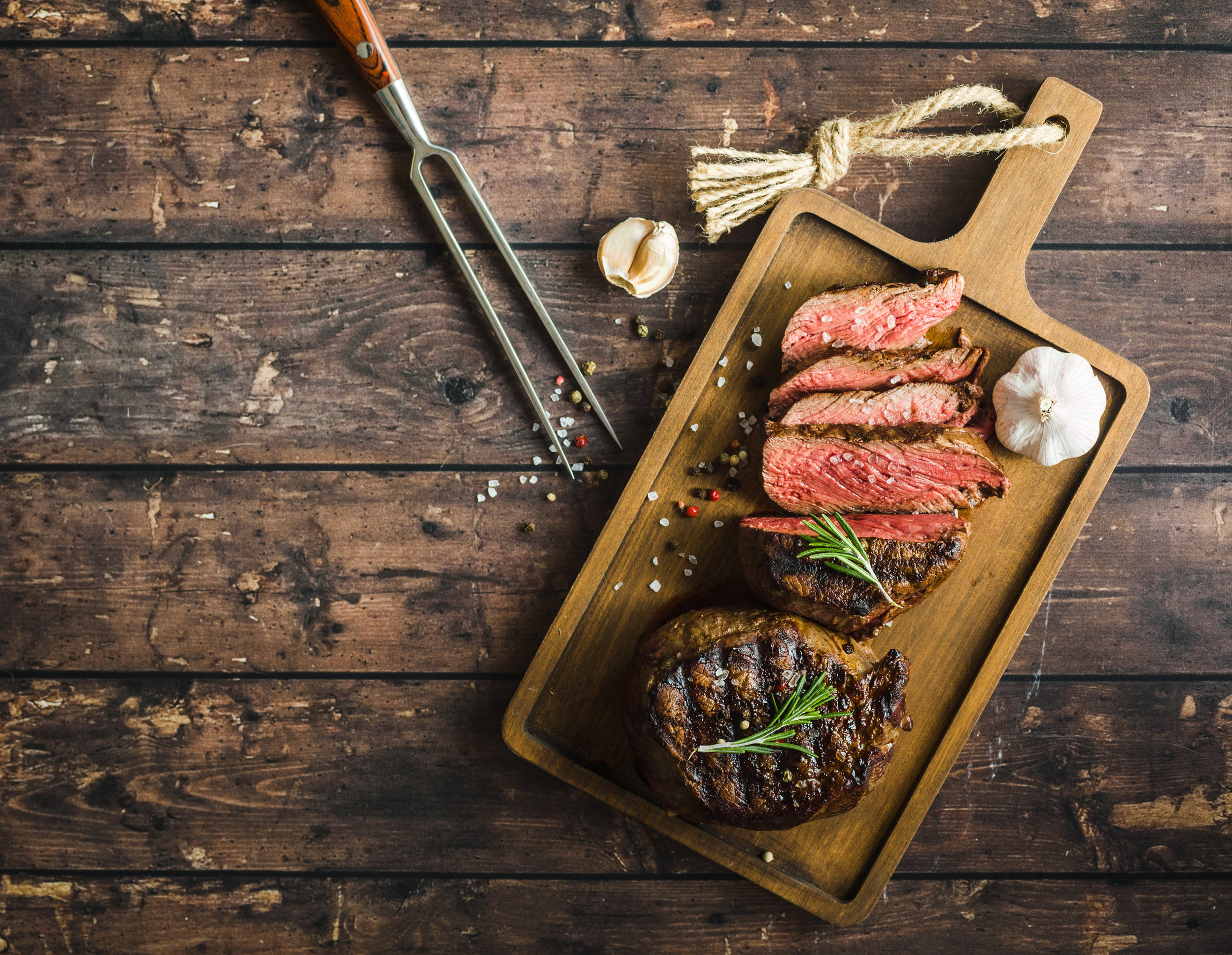 Sliced grilled marbled meat steak Filet Mignon seasonings fork wooden cutting board. Space for text. Juicy meat steak.jpg