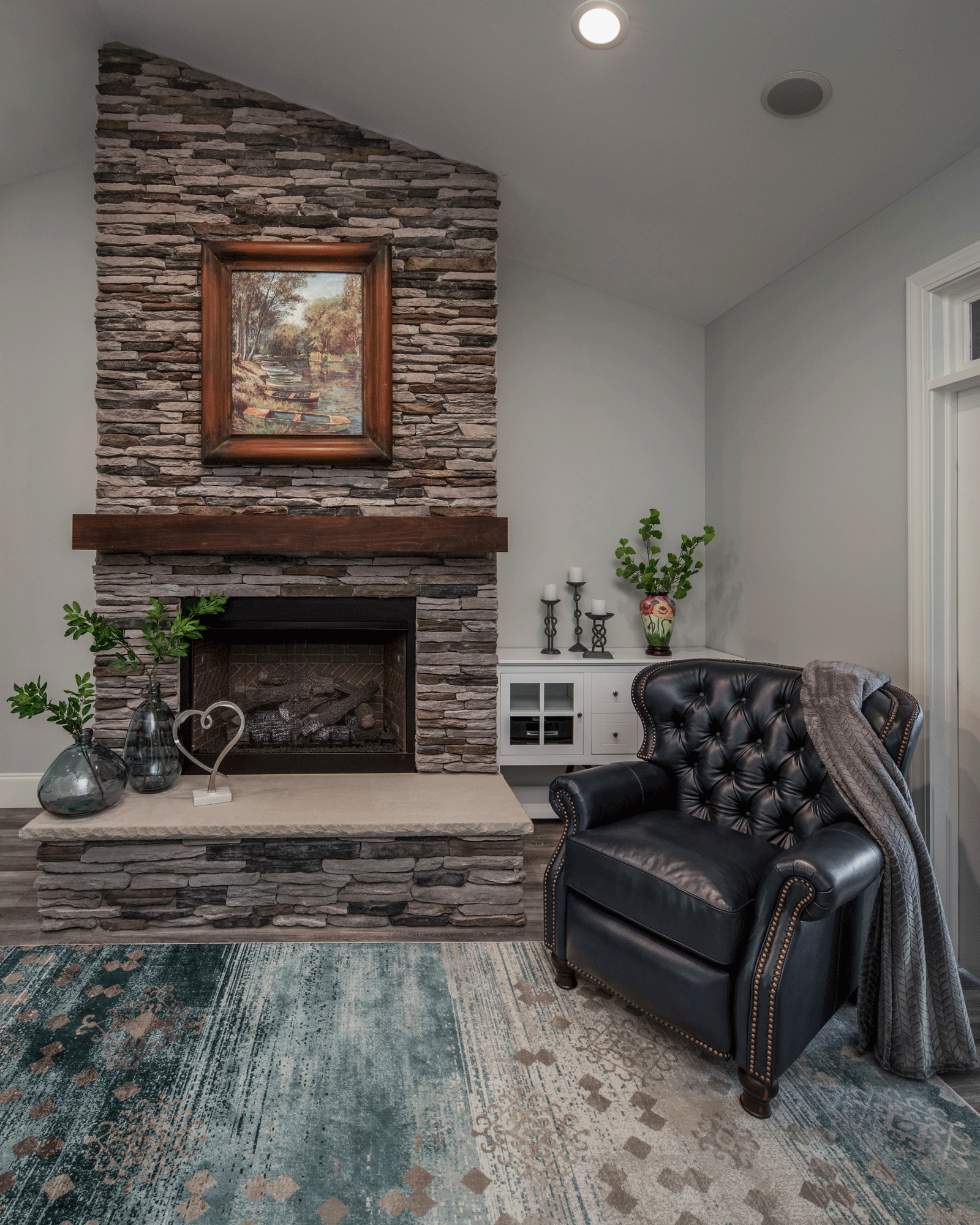 interior design for living room with flooring, furniture, seating, lighting, wall artwork, fireplace, and decor