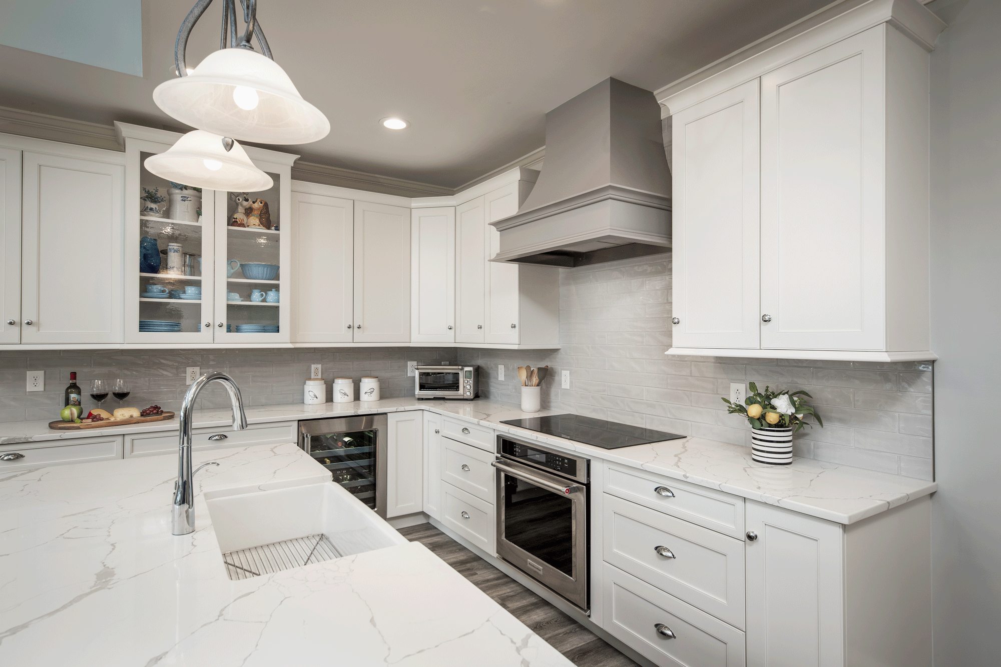 sleek kitchen remodel with flooring, cabinets, pendant lighting, recessed lighting, tile backsplash, island, seating