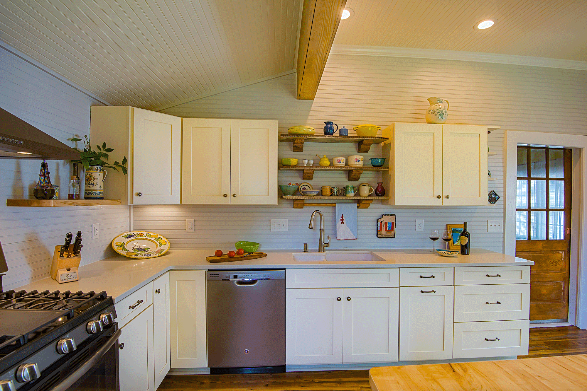 kitchen remodel with pendant lighting, expose beams, cabinets, wall treatment, island, decor