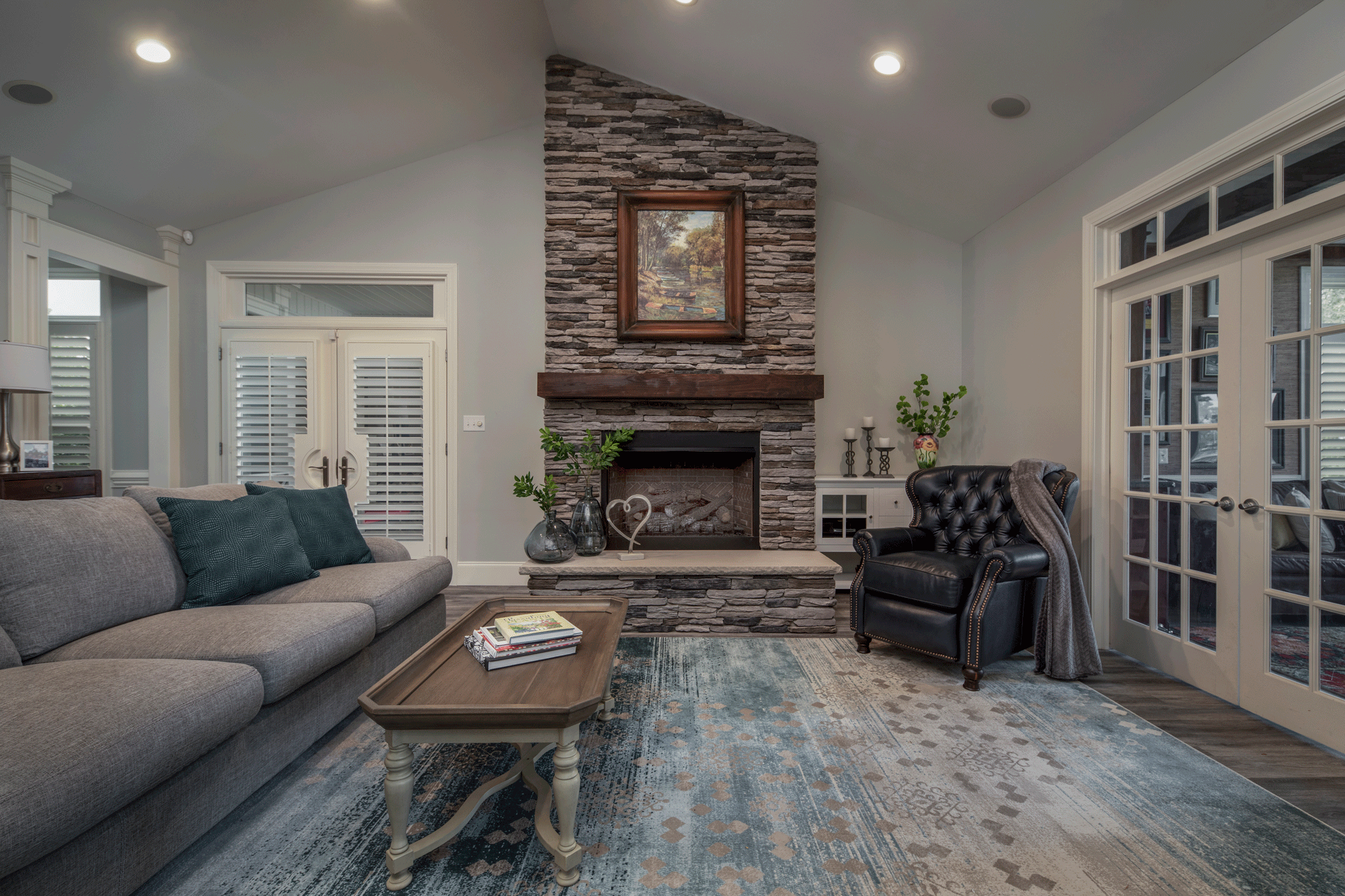 Living room design with stone fireplace, furniture, decor, and recessed lighting