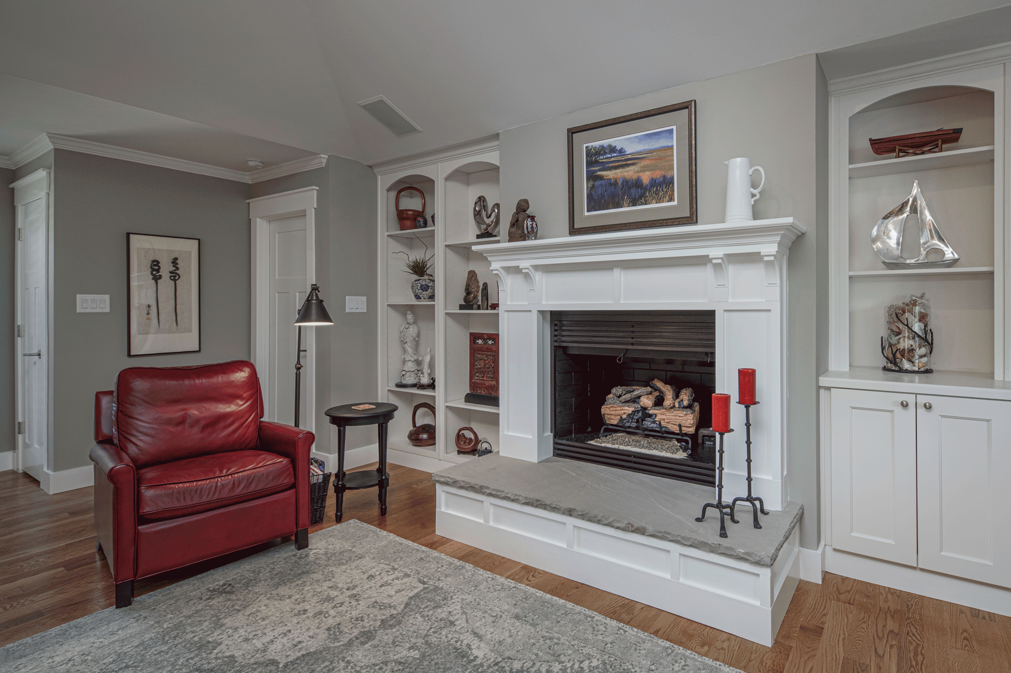 Living room design with built-in shelves, decor, seating, fireplace, creative lighting