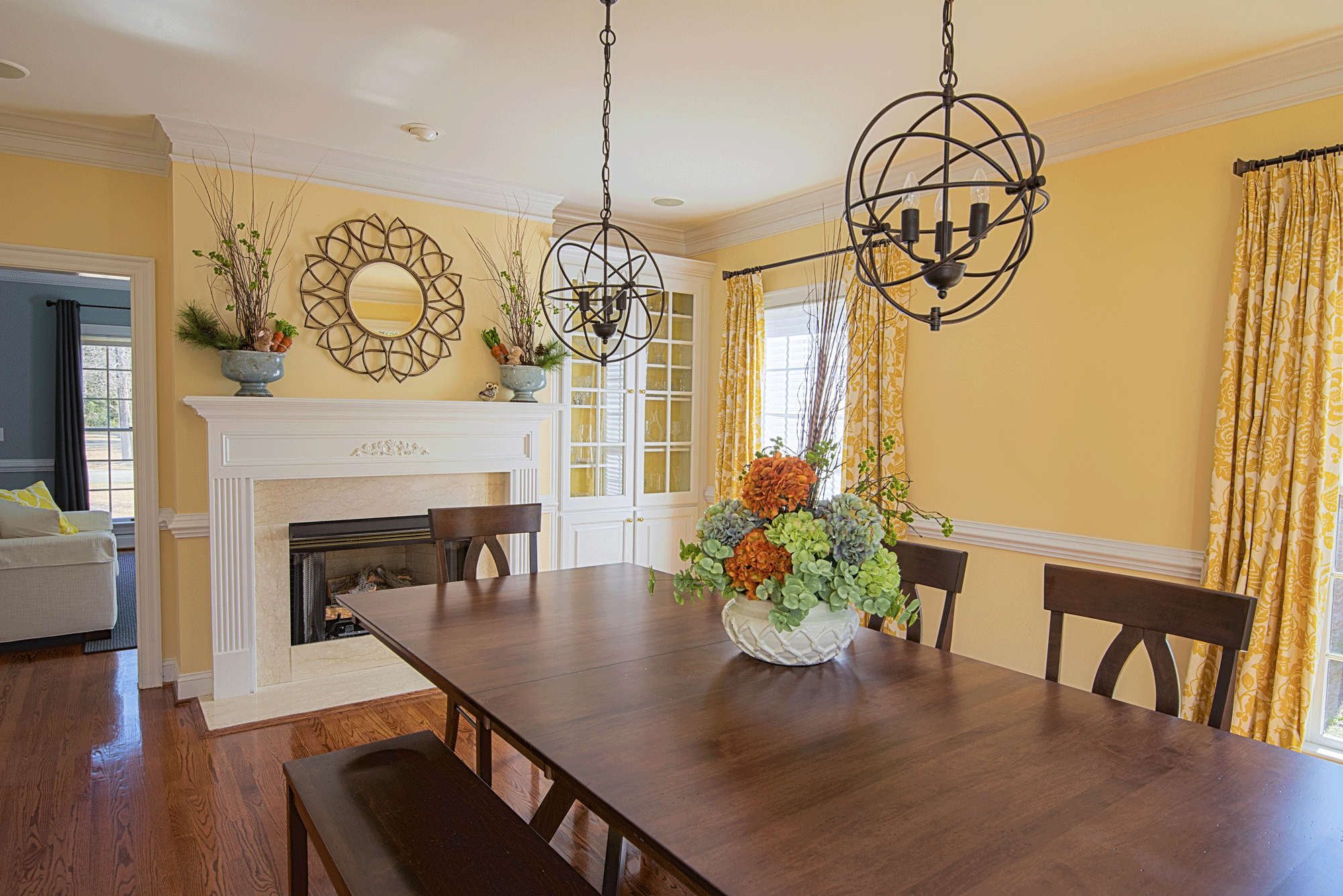 Dining room design with wall decor, mantle, fireplace, table decor, and pendant lights