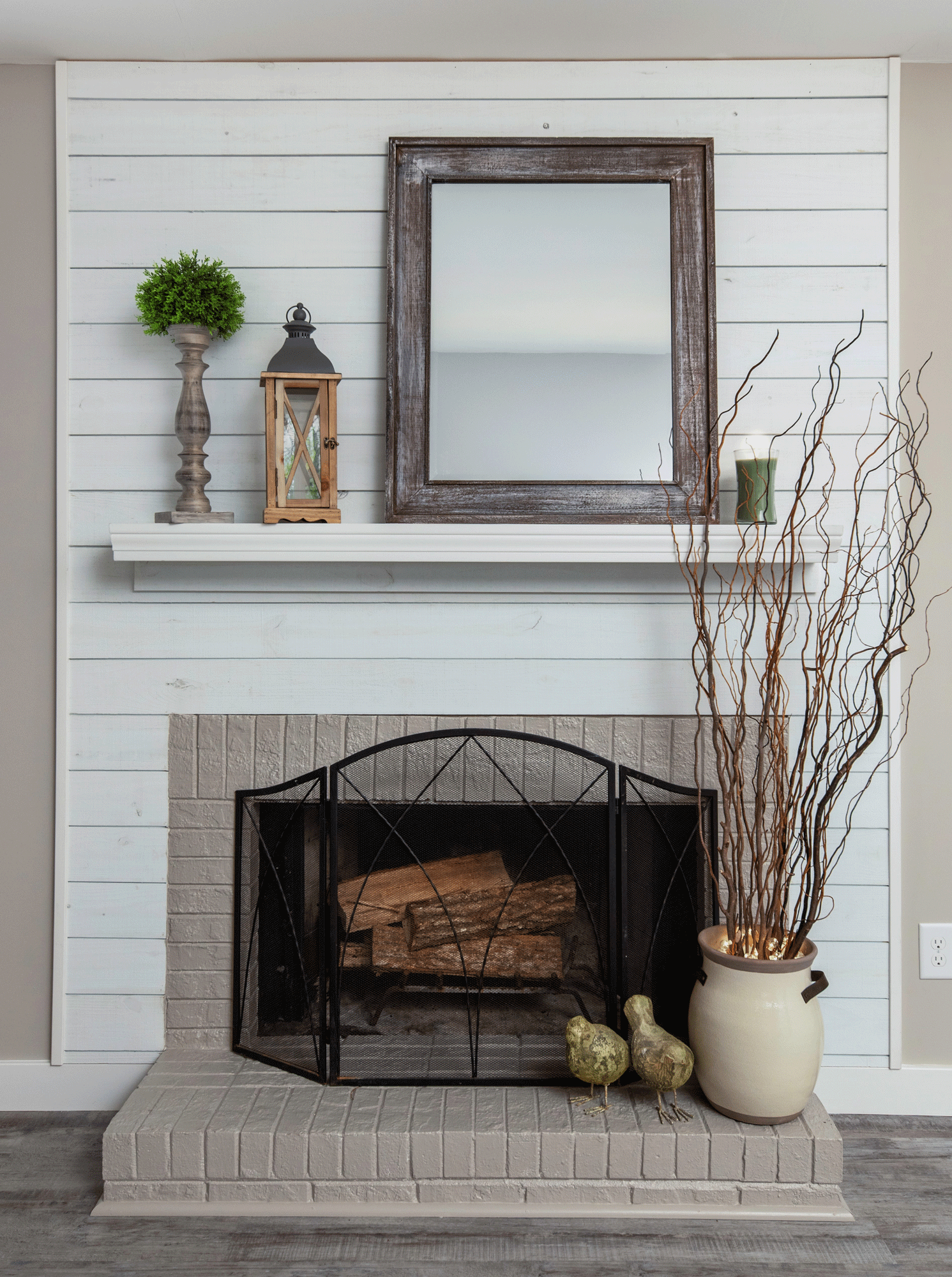 Fireplace mantle decor with branches, rustic frames, lantern