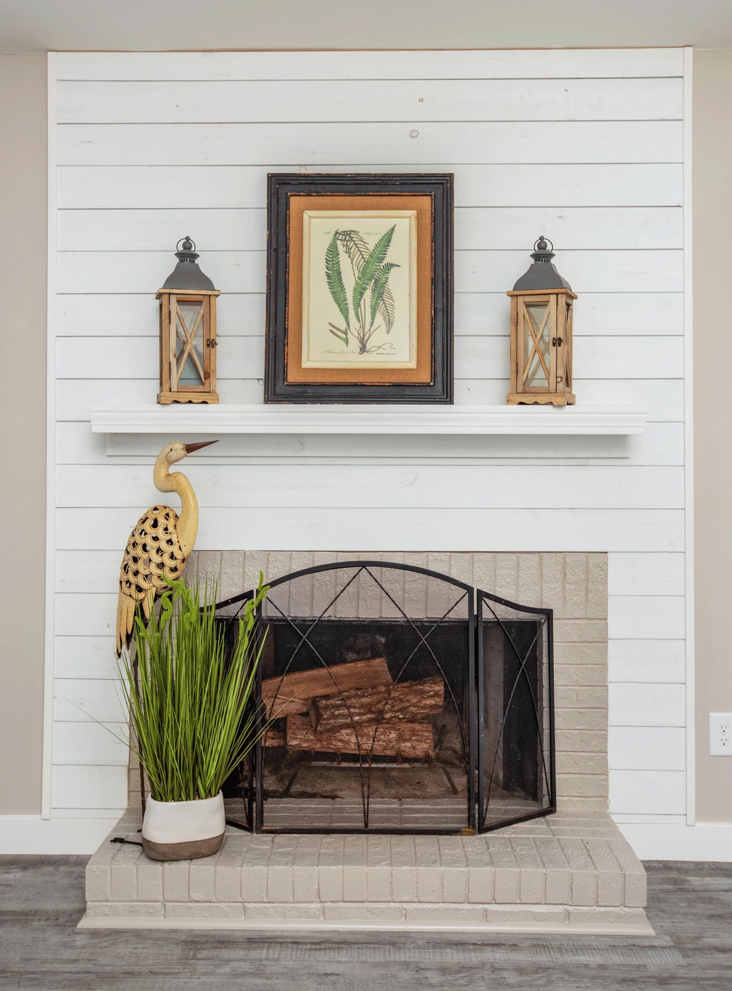 Fireplace mantle decor with artwork, lanterns, crane bird, grass planter